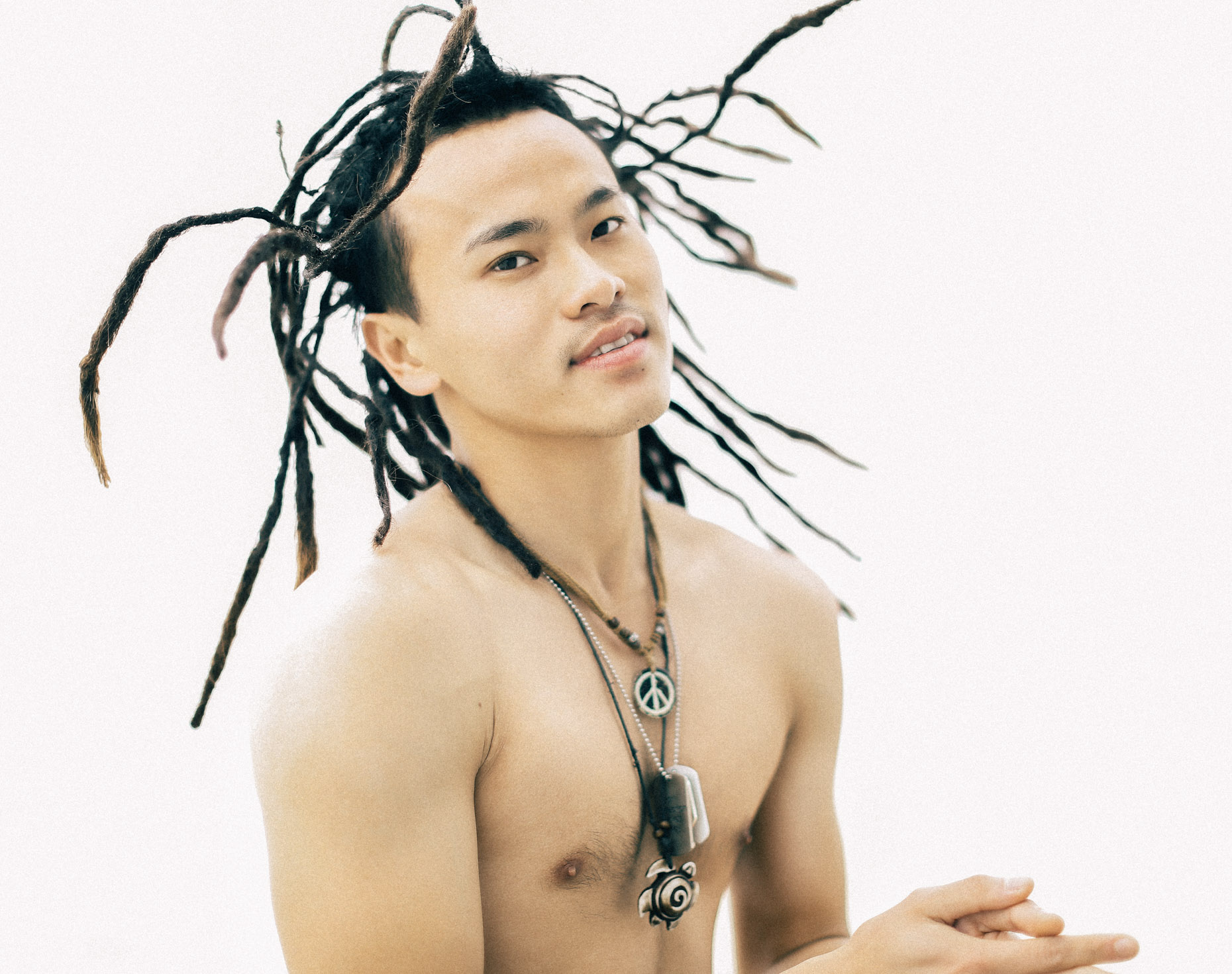 Shirtless asian man with dreadlocks and many necklaces