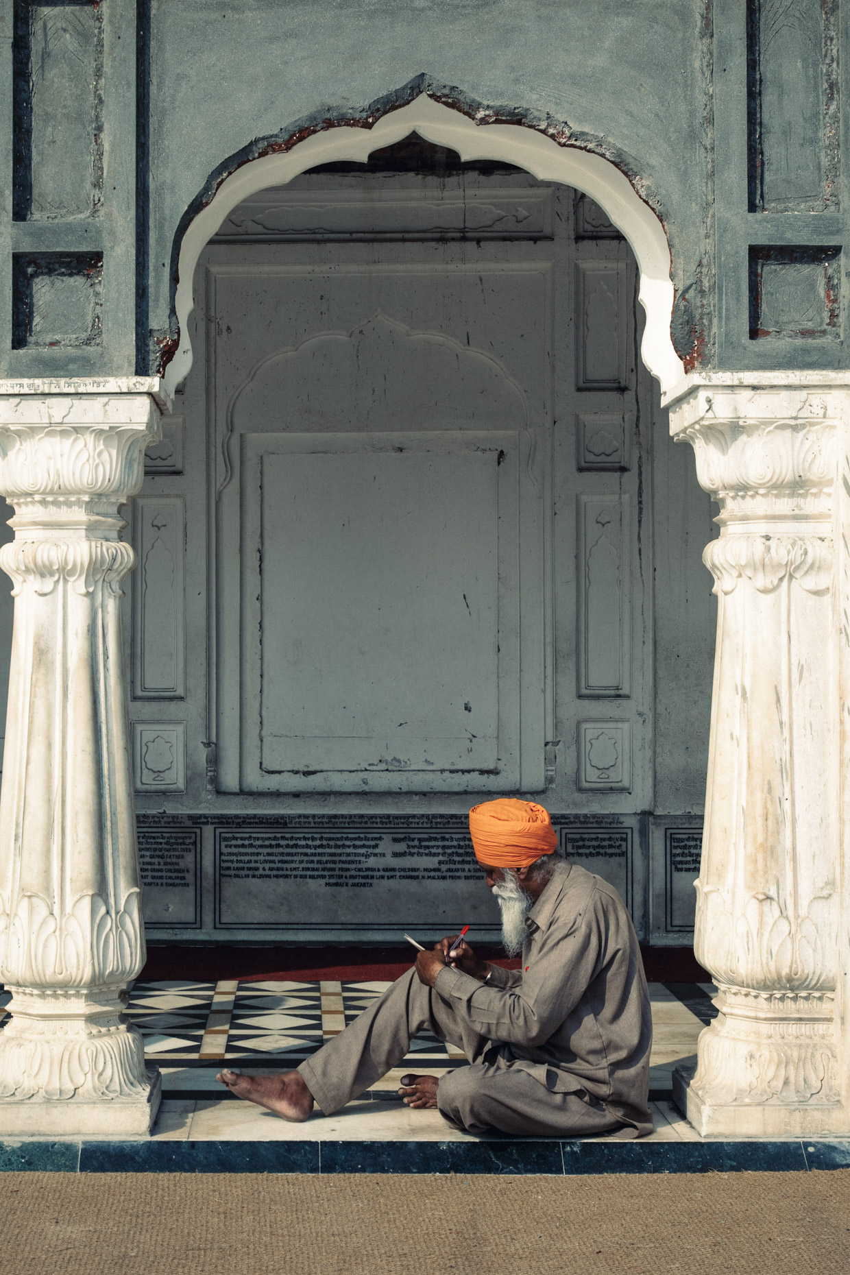 Sikh man in orange turbon sitting in doorway at golden temple in Amritsar, Punjab,  India