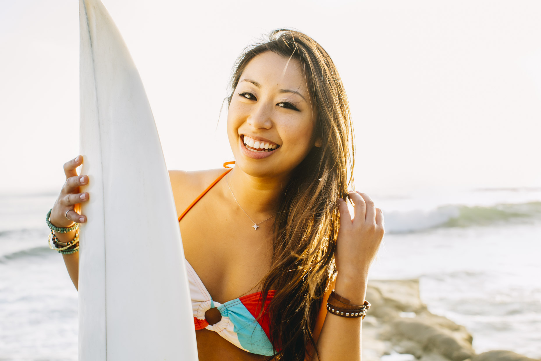 Smiling Asian woman in bikini at beach holding surfboard