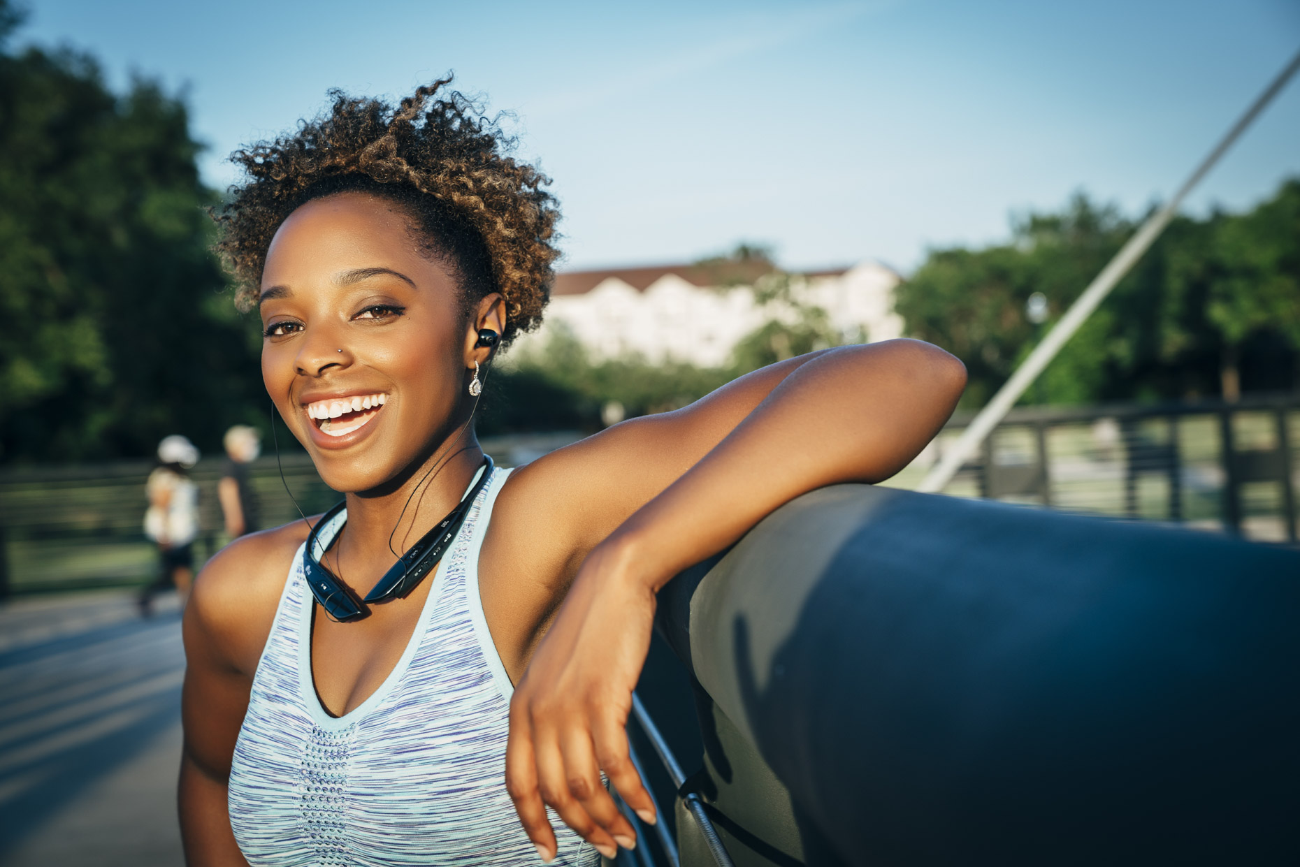 Smiling black woman in fitness attire and wireless headphones