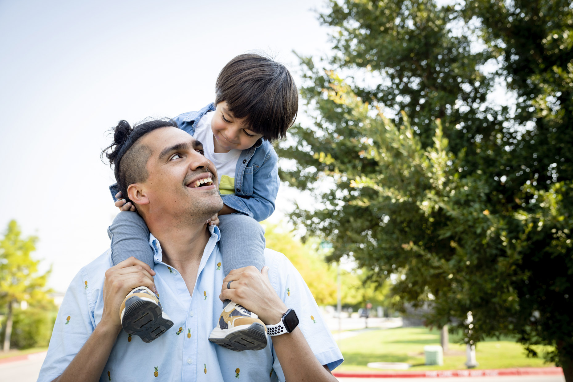 Smiling dad carrying son on shoulders