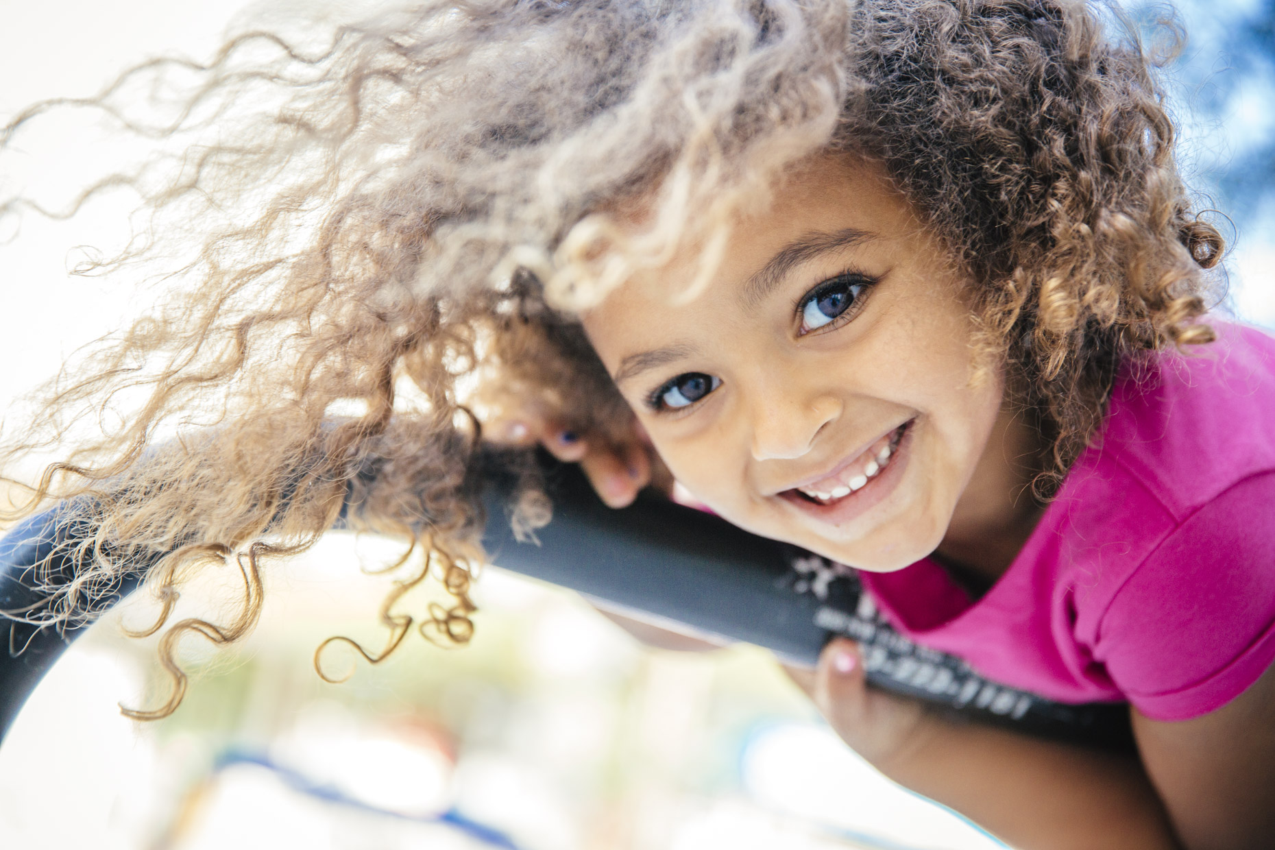 Smiling girl with curly hair hanging upside down