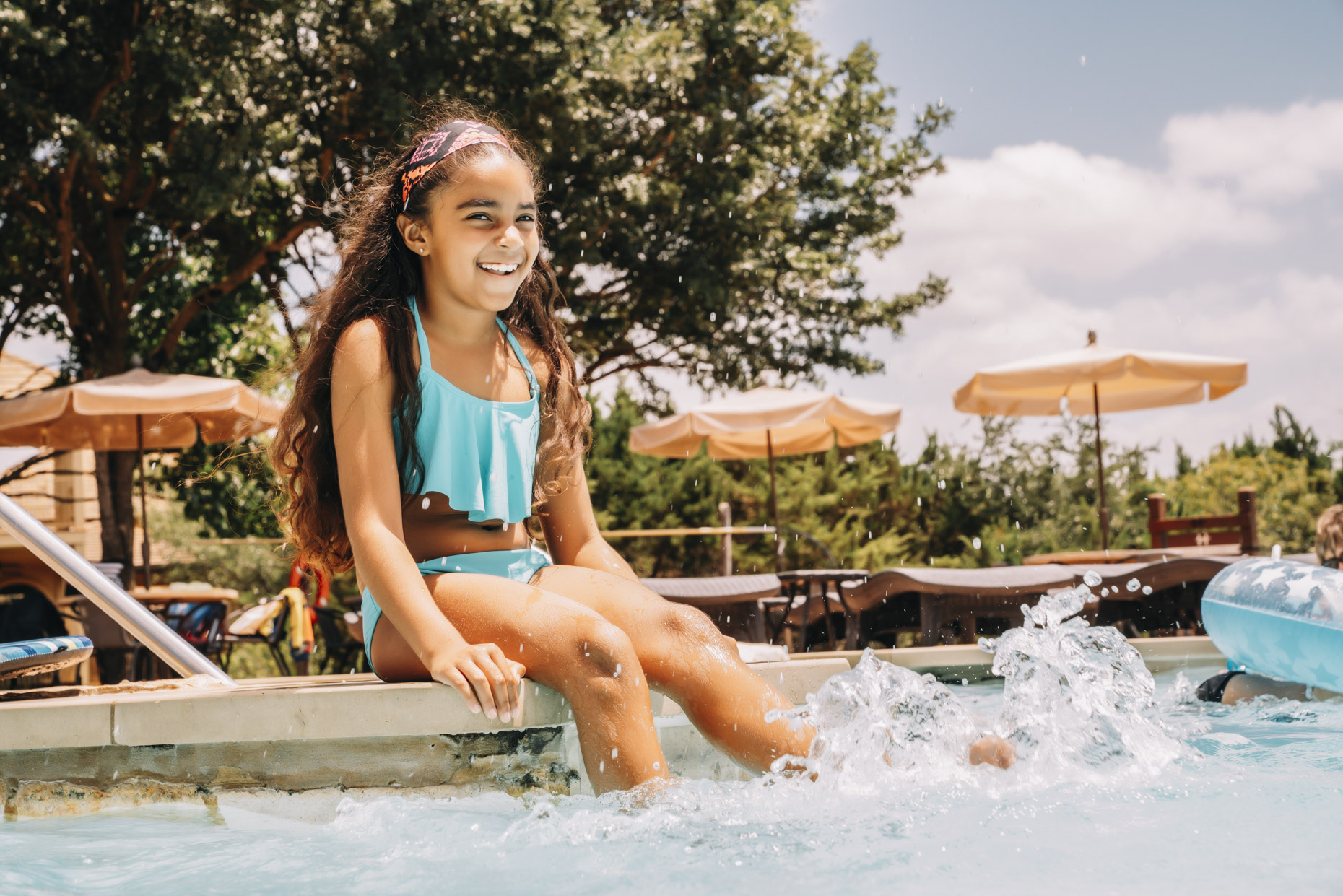 Smiling hispanic girl sitting poolside kicking water in pool