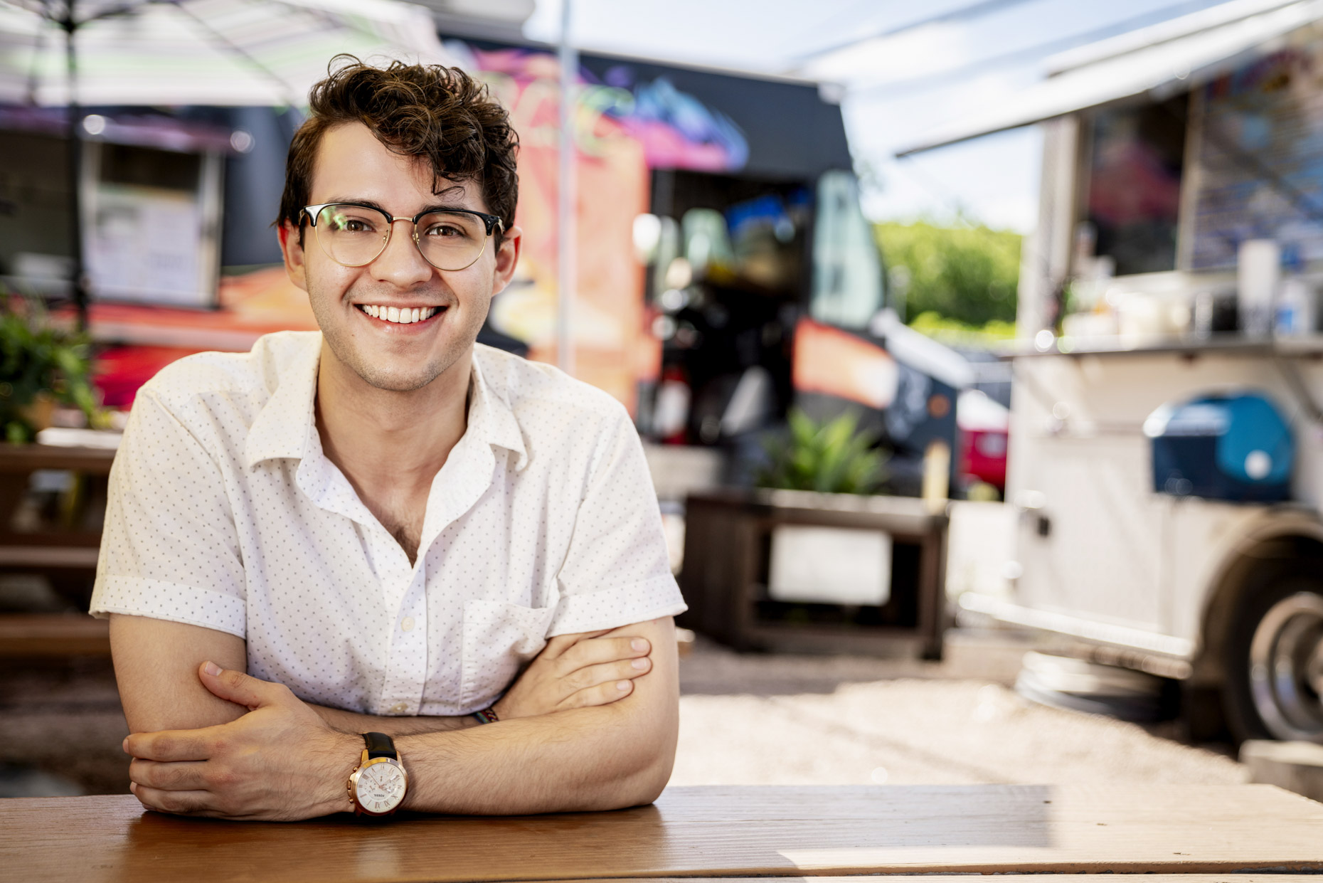 Smiling man in glasses sitting in front of food truck