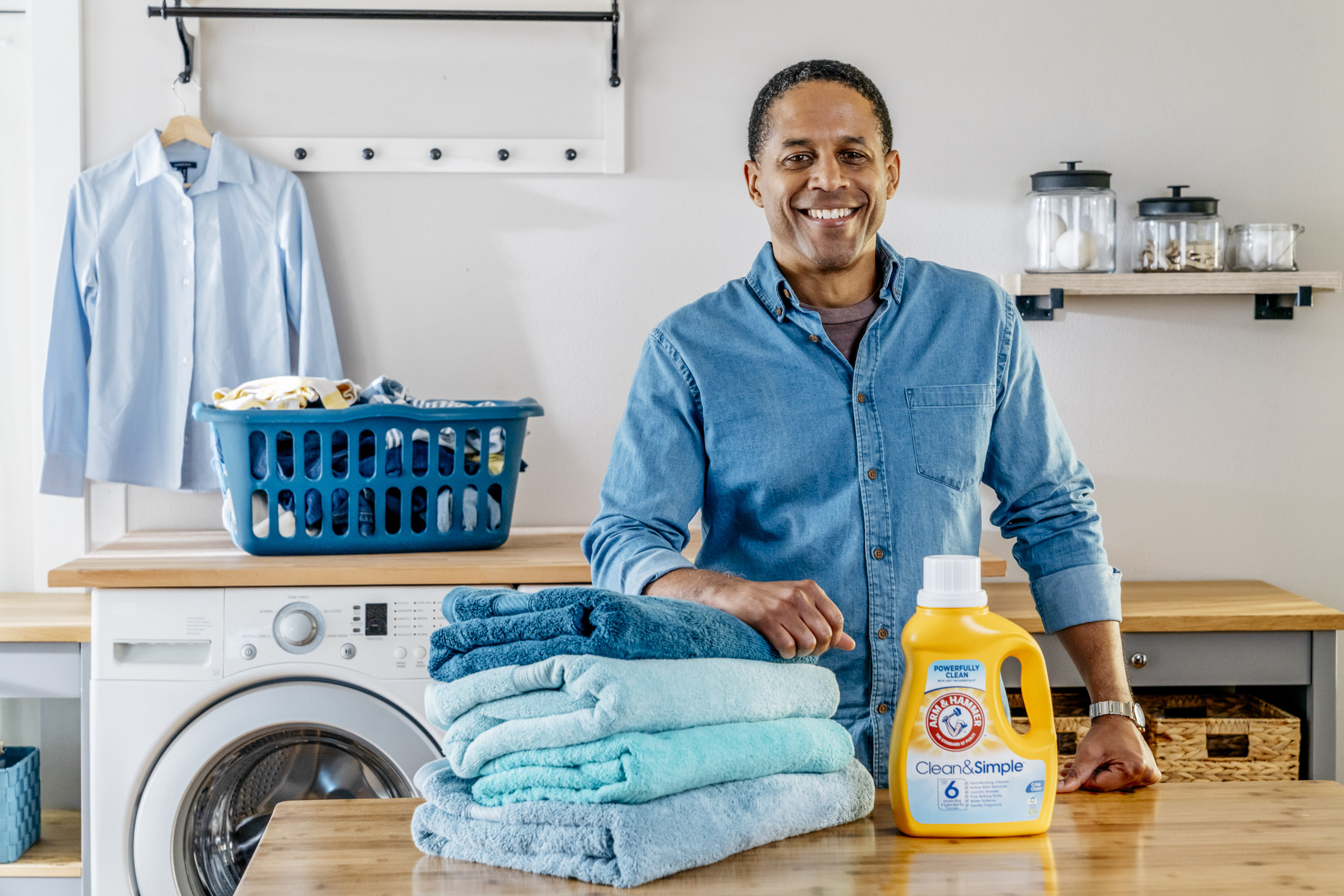 Smiling man with bottle of Arm and Hammer detergent and folded towels