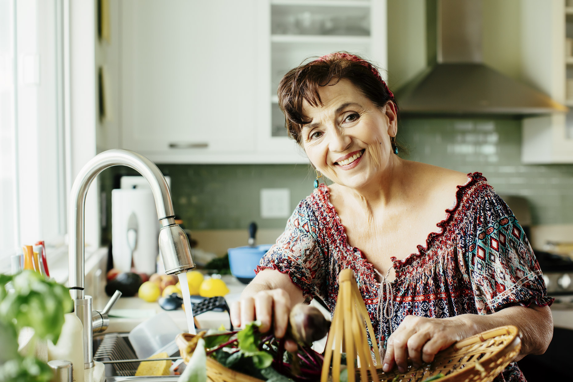 Smiling senior latinx woman in kitchen with vegetable basket