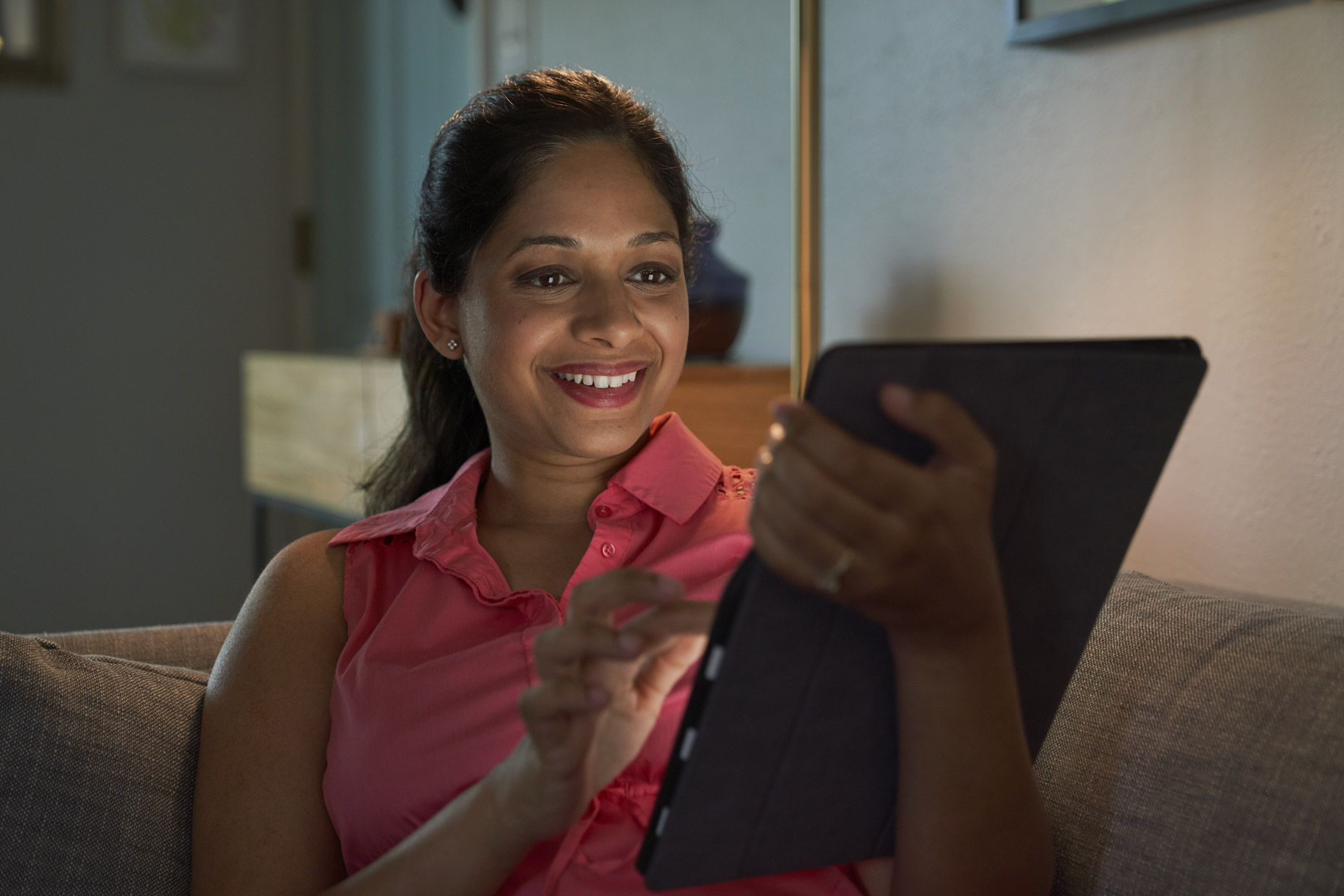 Smiling woman with face lit by ipad tablet computer