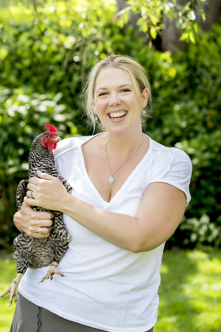 Smiling woman holding chickent in garden