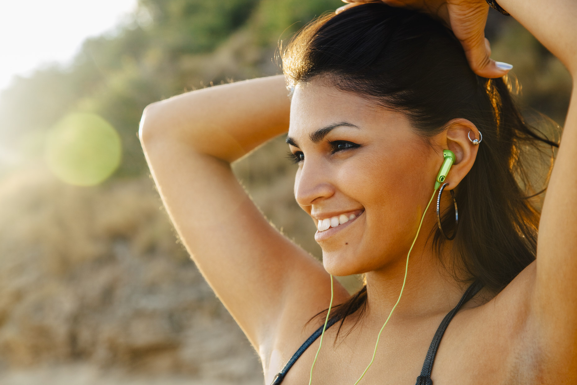 Smiling woman in sunlight listening to green headphones