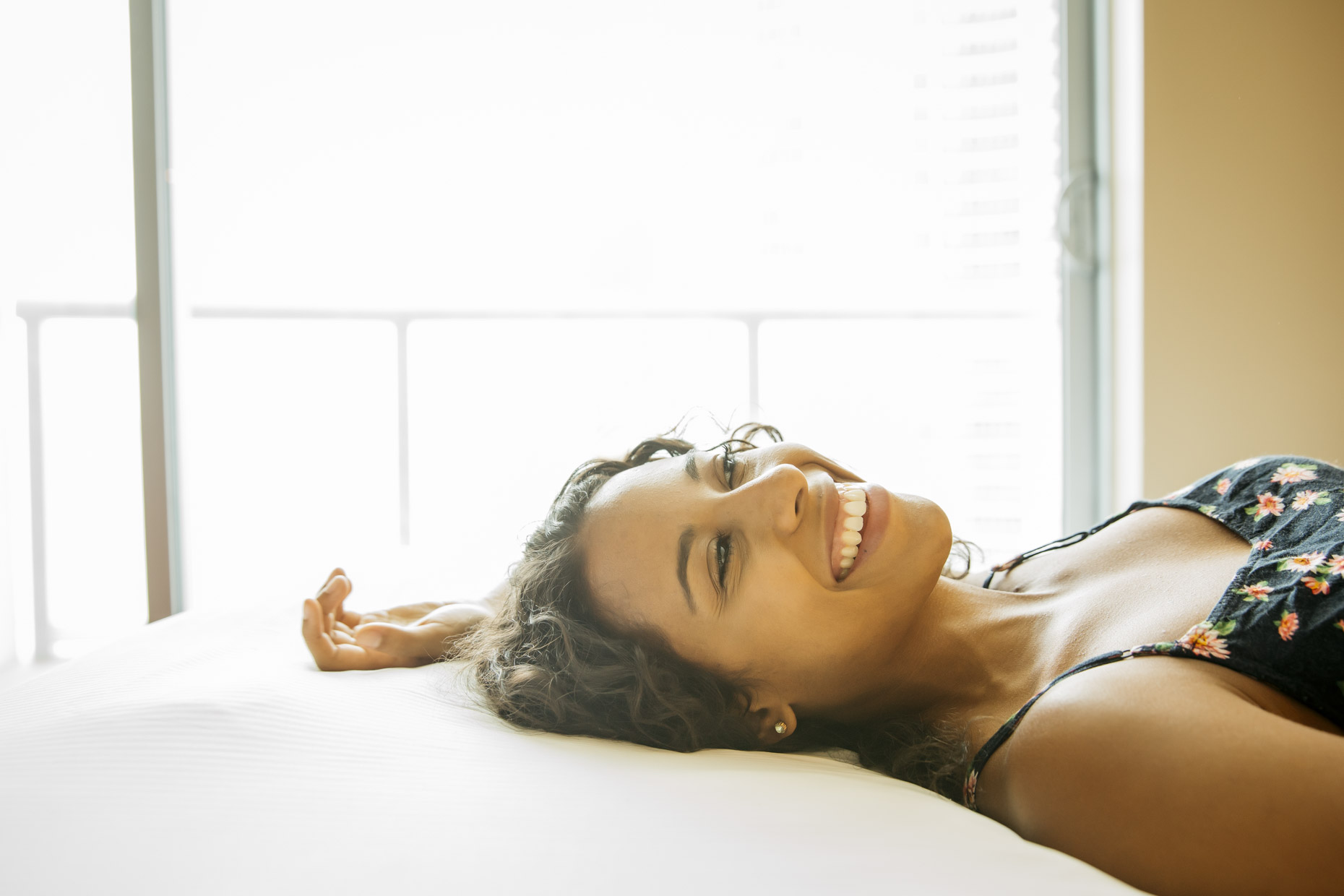 Smiling woman laying on her back on bed in hotel room