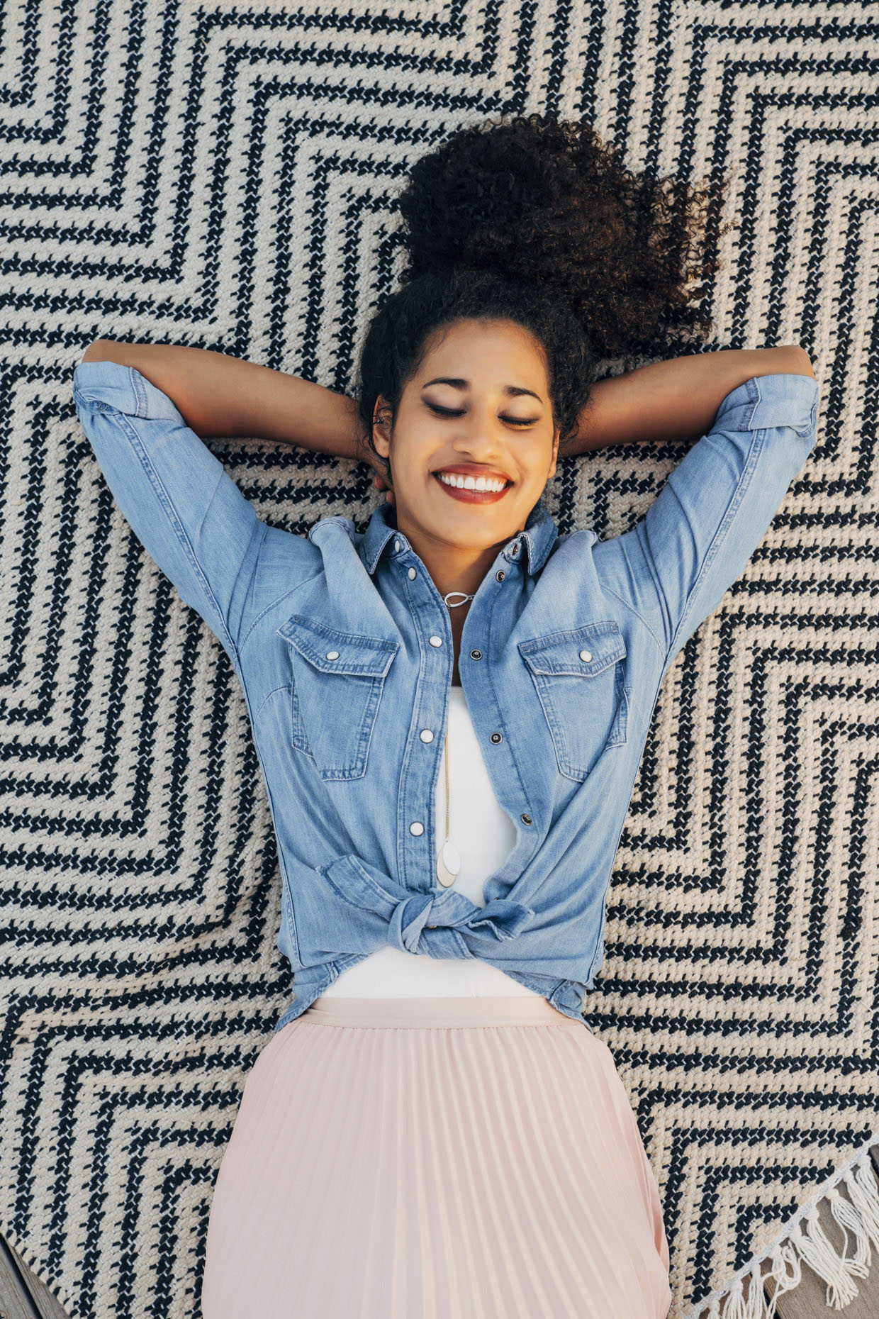 Smiling woman laying on rug with eyes closed