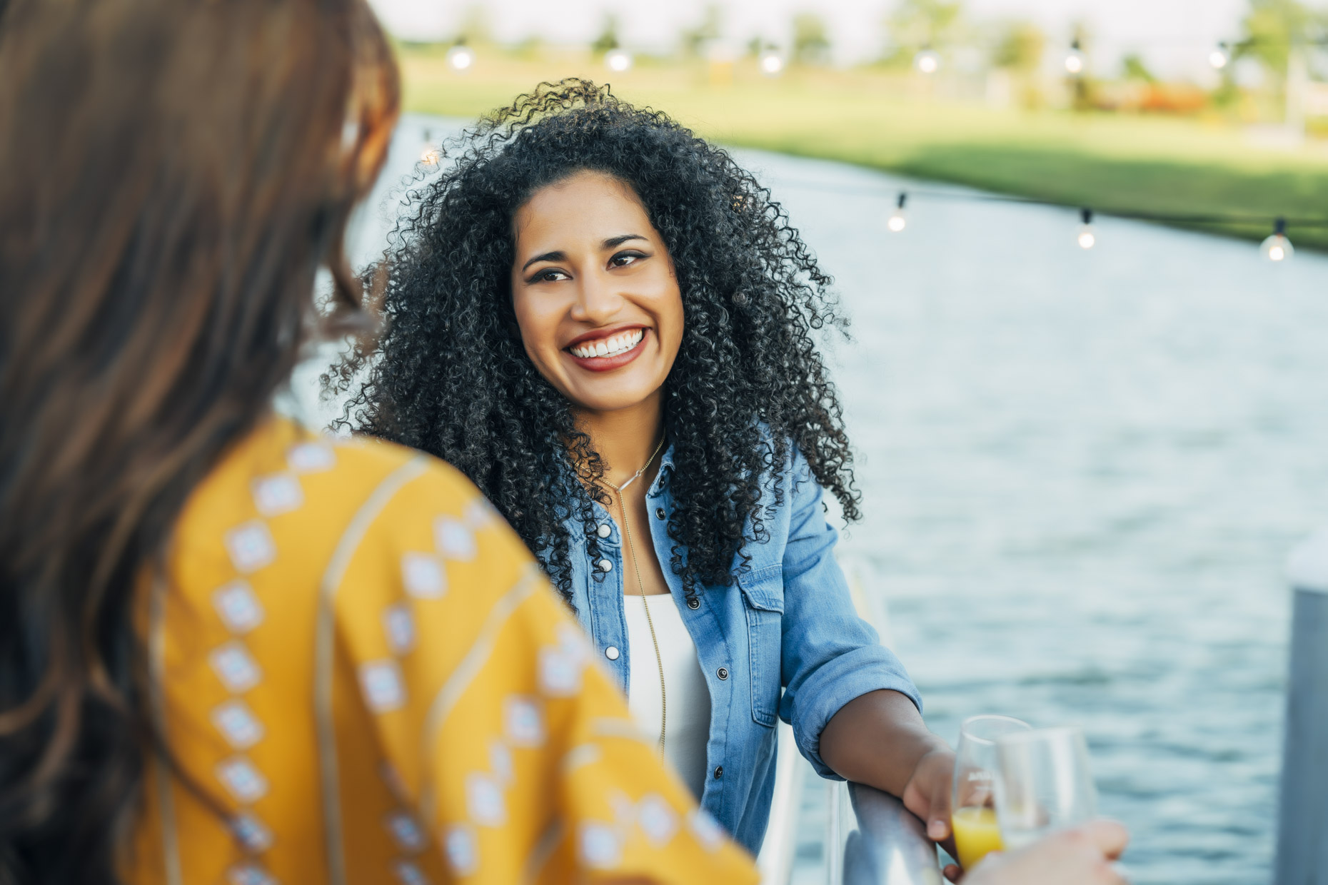 Smiling woman with big curly hair talking to friend by lake