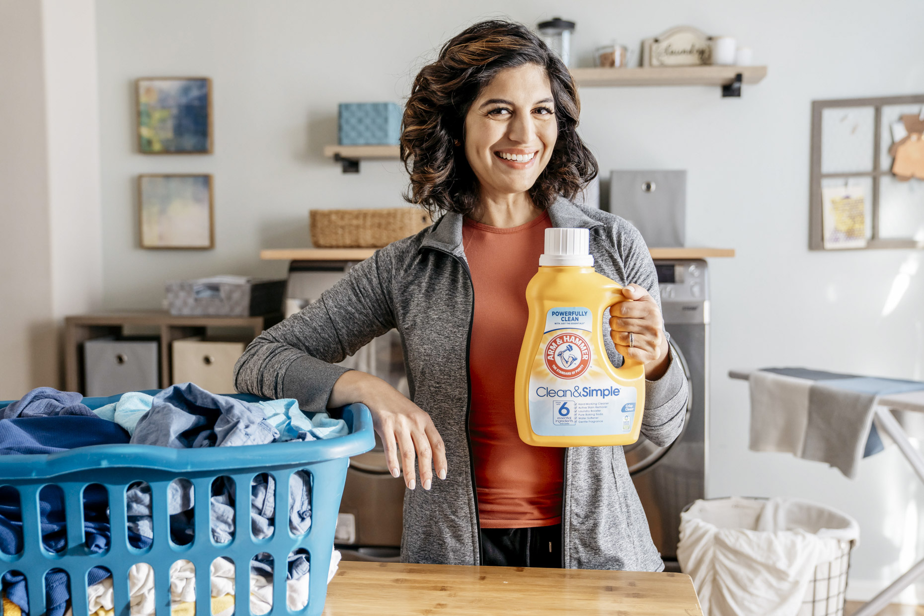 Smiling woman with bottle of Arm and Hammer detergent and basket of laundry