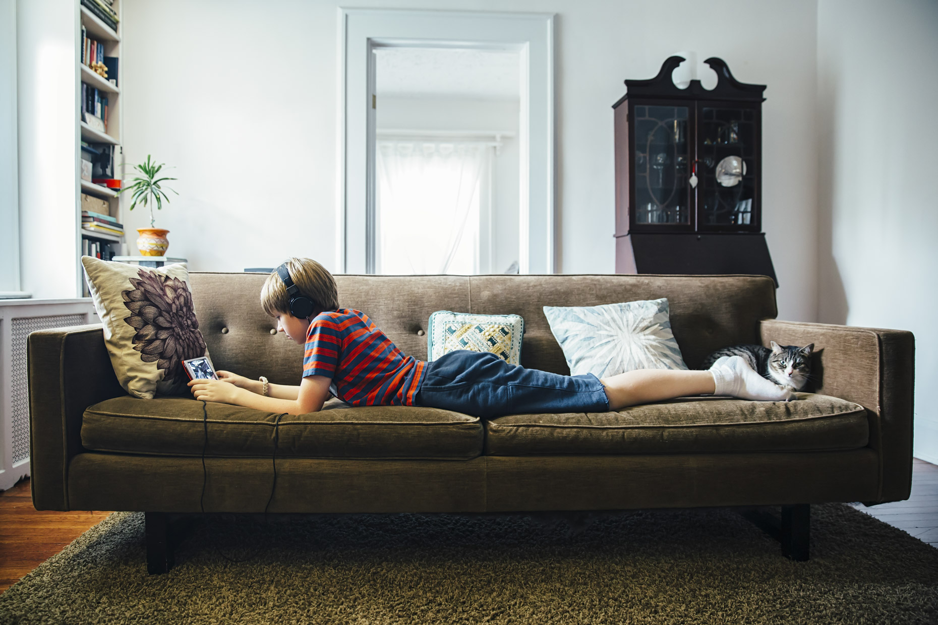 Inti St Clair photo of tween boy laying on couch watching video on ipad with cat at his feet