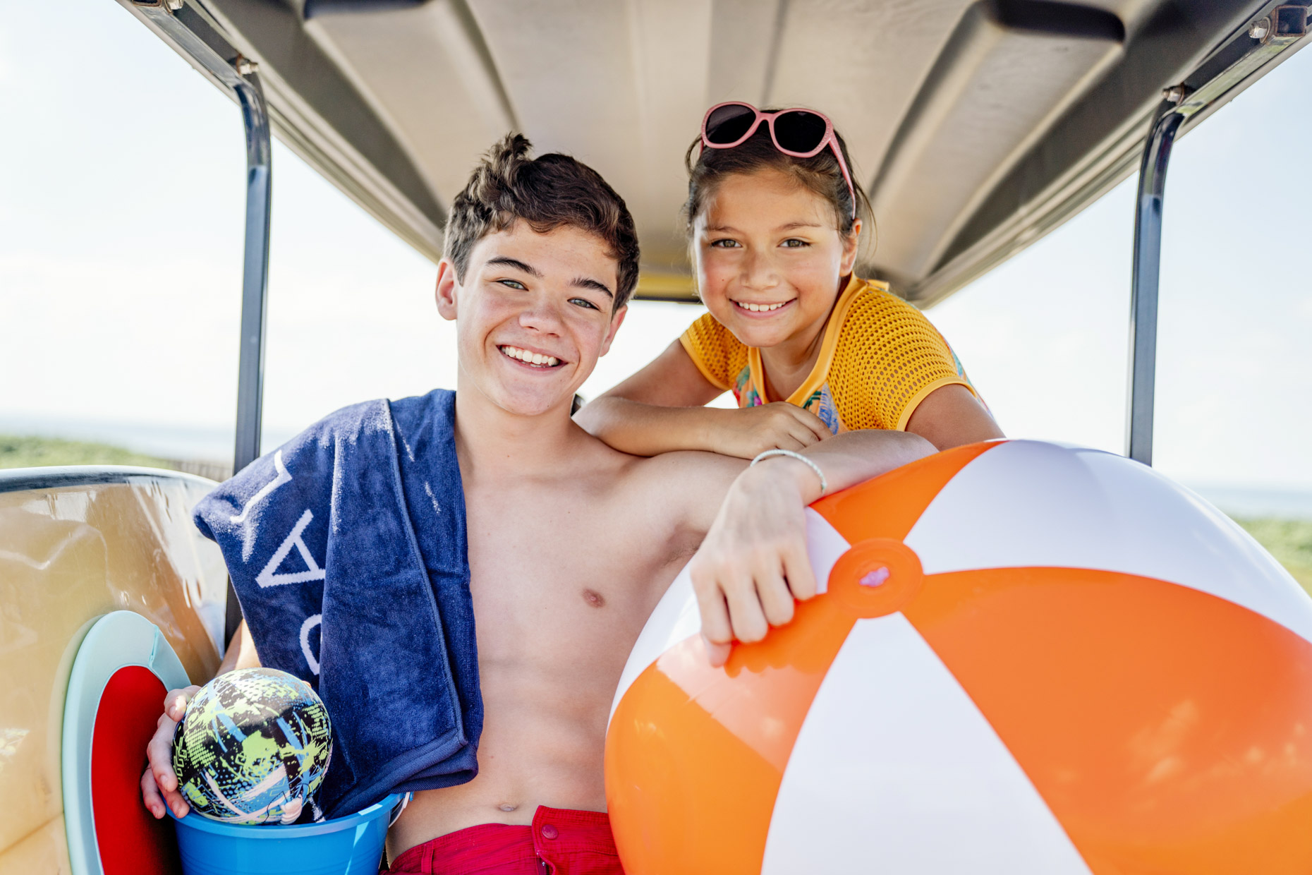 Teen boy and sister on golf cart with beach ball and surfboard