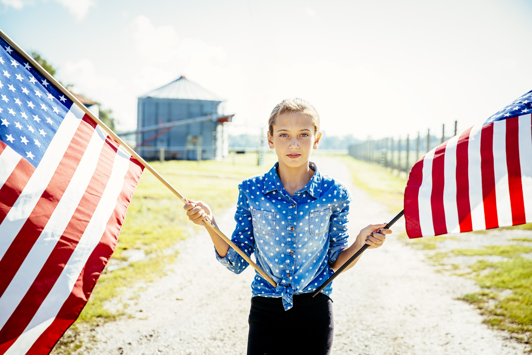 Teen girl holding american flags in front of grain silo on ranch