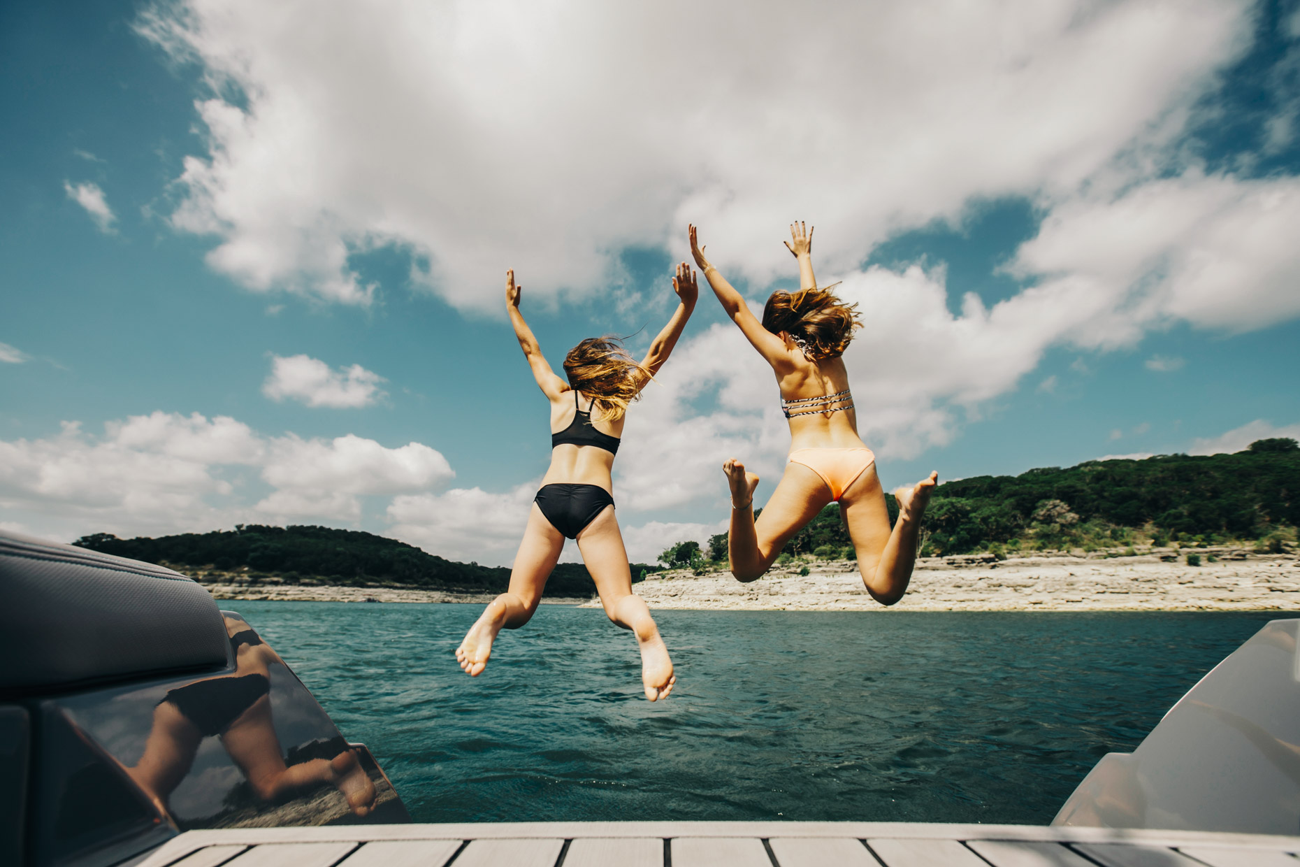 Teen girls jumping off of boat into lake