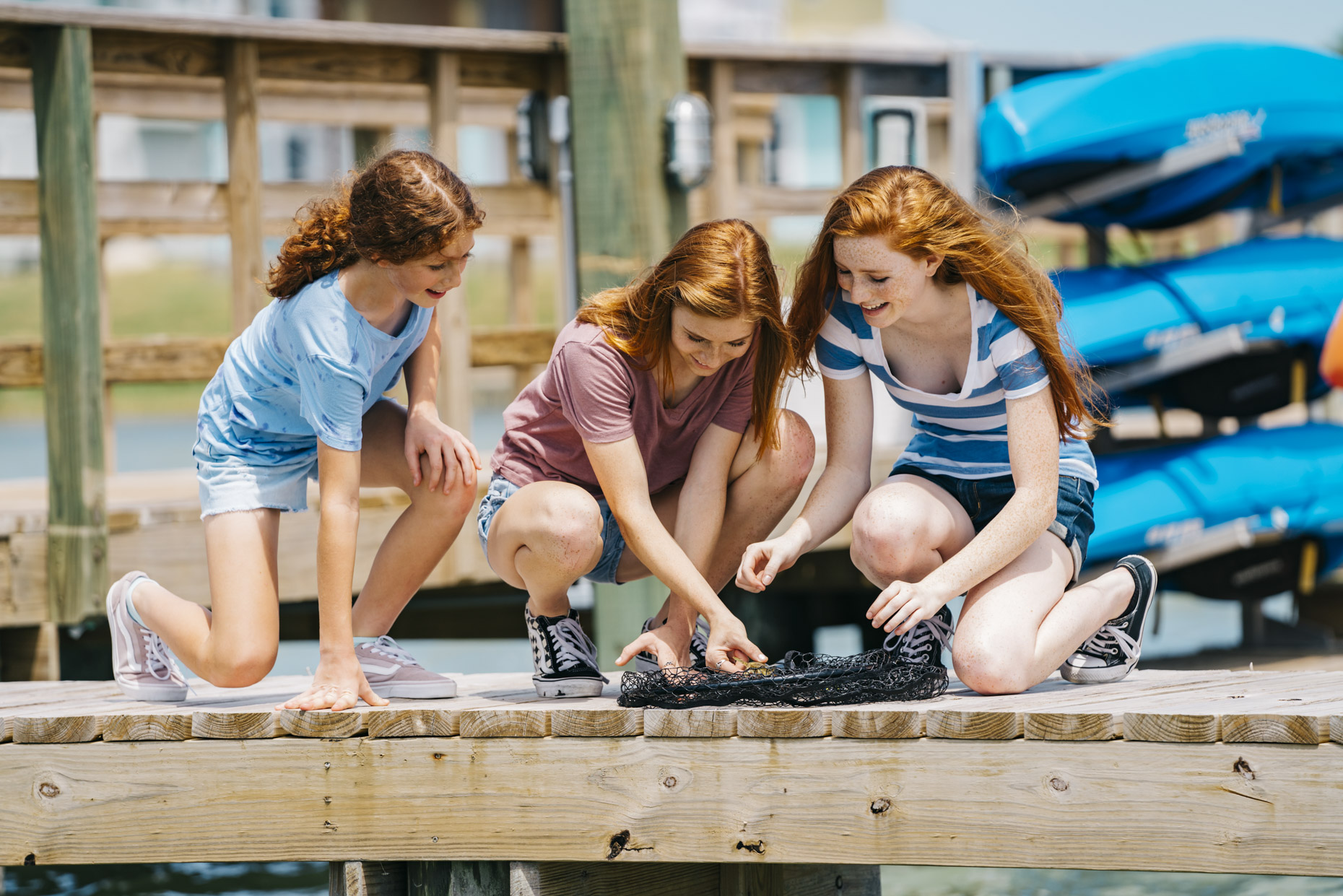 Teen girls on dock looking at freshly caught fish in net