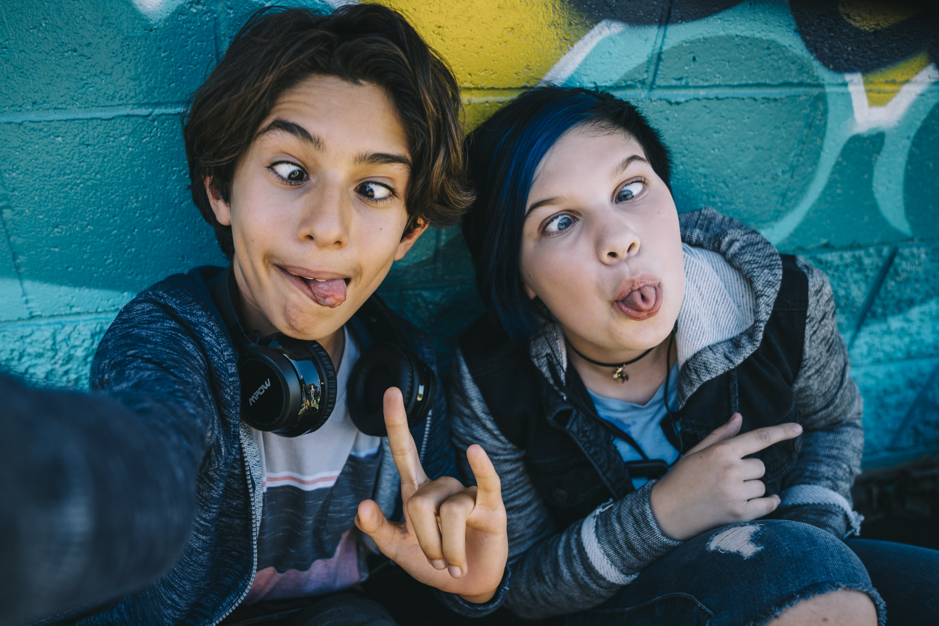 Teens making goofy faces while taking selfie photo