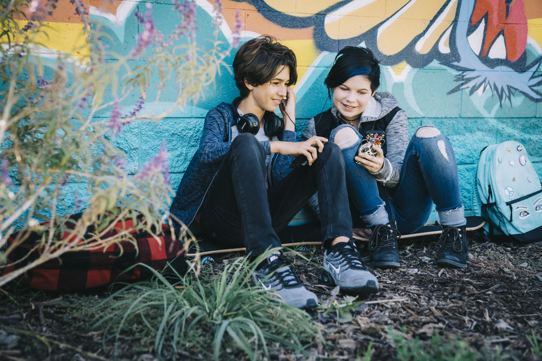 Teens sitting by grafitti wall watching video on phone together