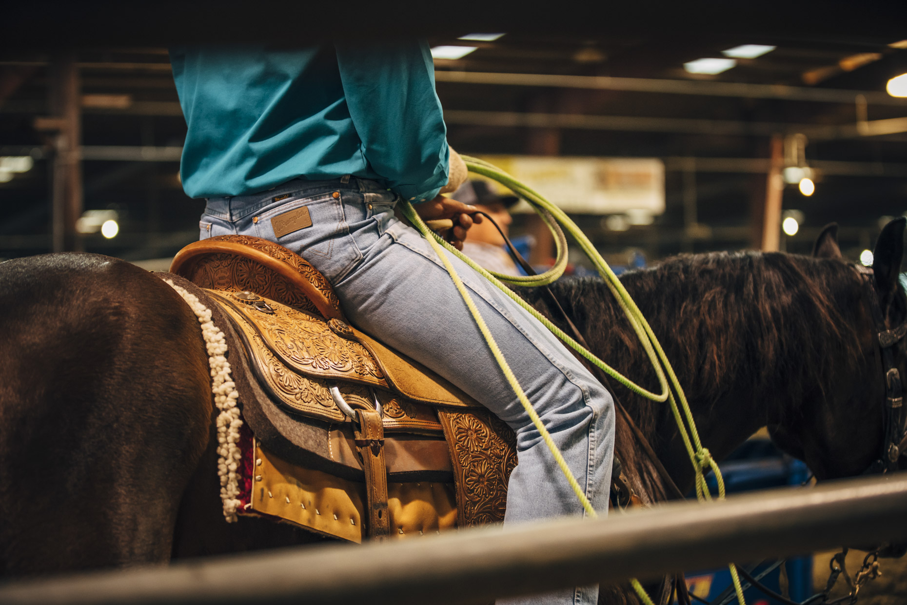 Tight butt shot of man wearing wrangerl jeans riding horse in rodeo