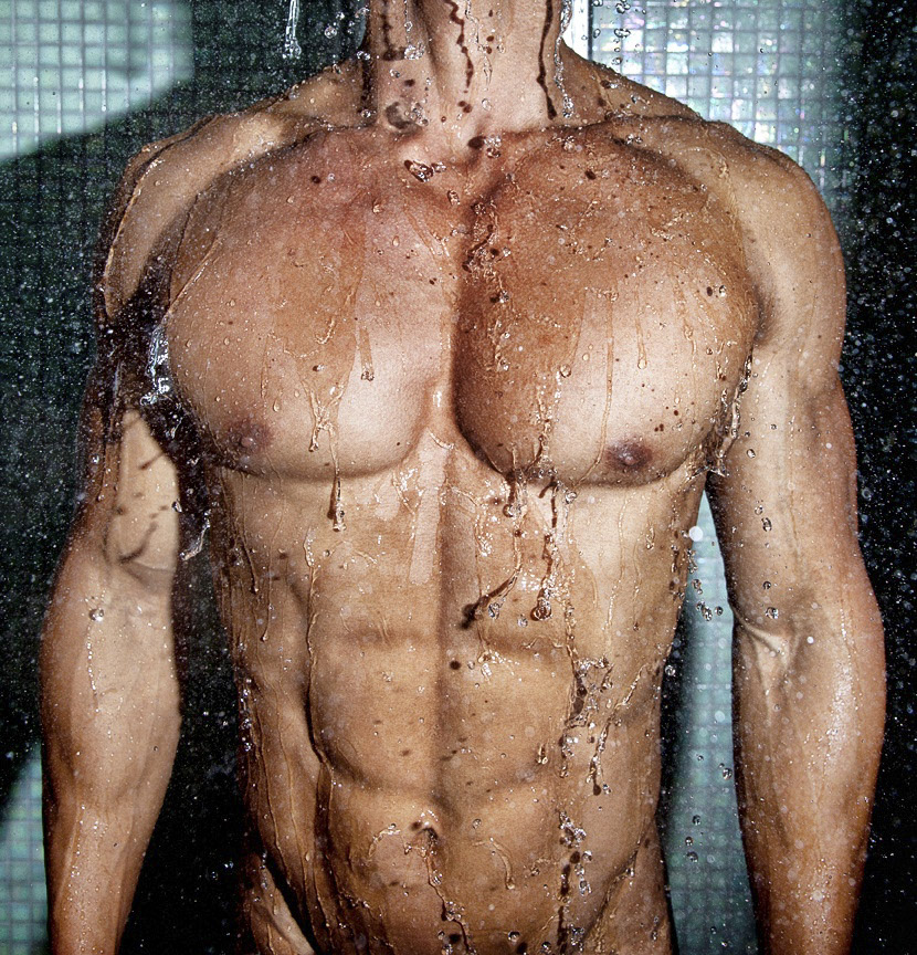 Torso of fit male body in shower
