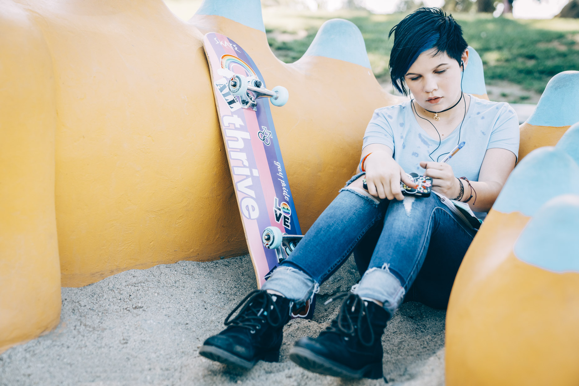 Transgender teen with skate board and headphones sitting in park journaling