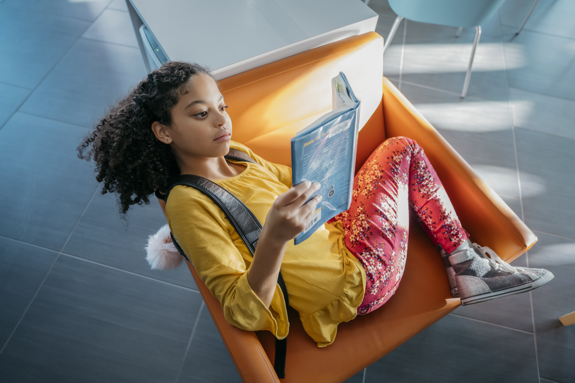 Tween girl reading book curled up in library chair
