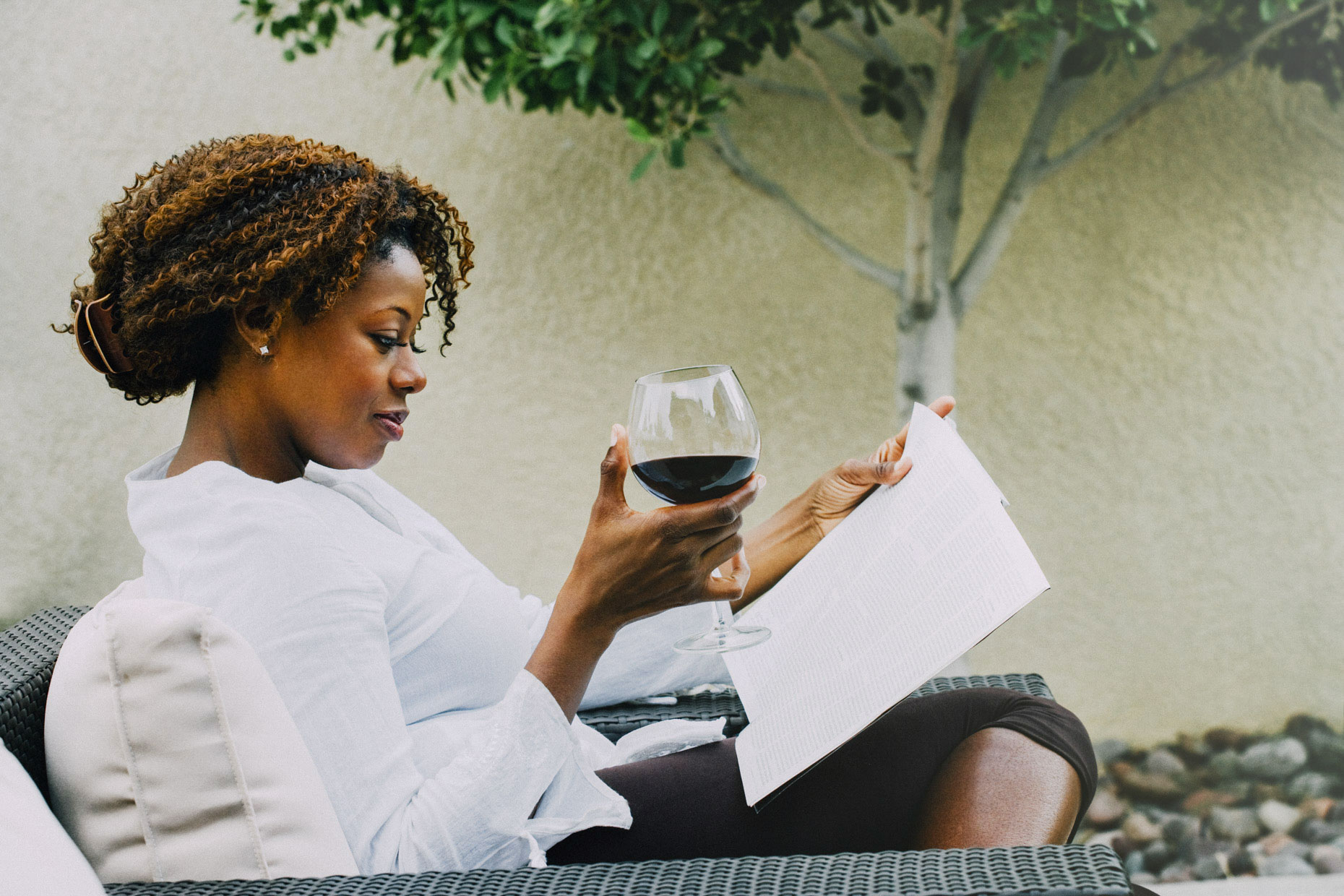 Black woman sitting on patio drinking red wine and reading book shot by Inti St. Clair