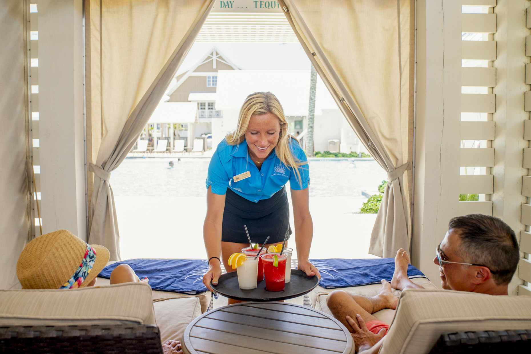 Woman delivering drinks to guests in private pool cabana