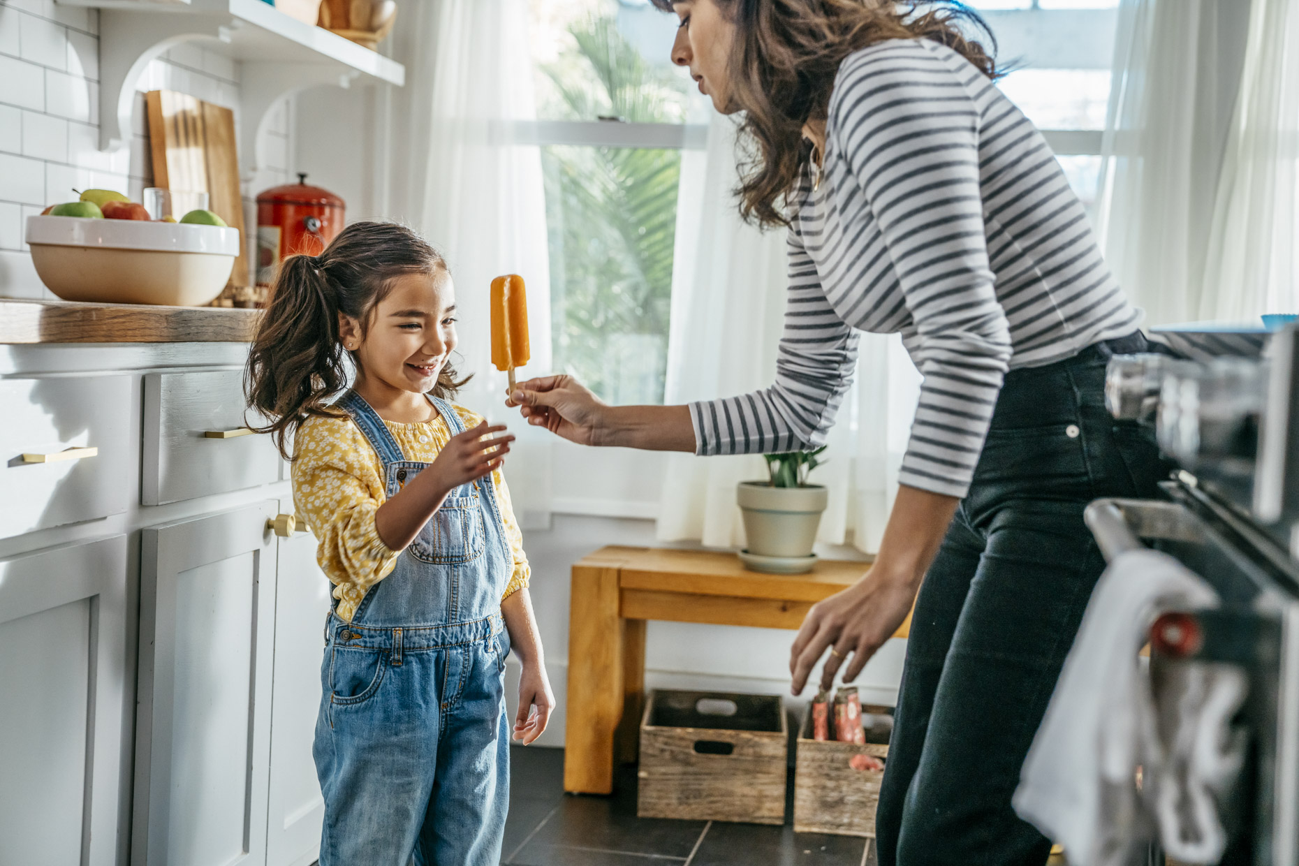 Woman handing smiling girl popsicle in kitchen