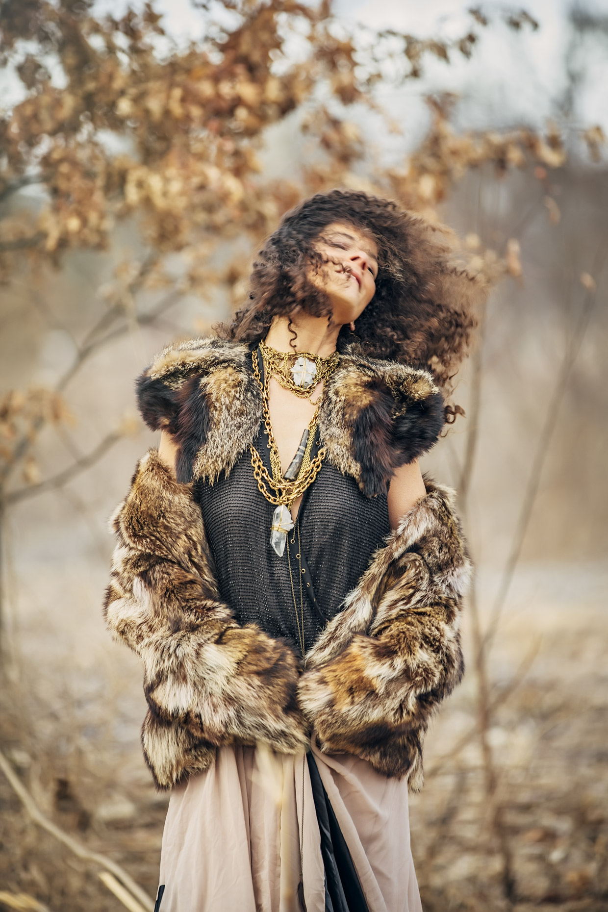 Woman with head back in long dress and fur coat with brass and white crystal Belthazzar Jewels necklaces outside in fall