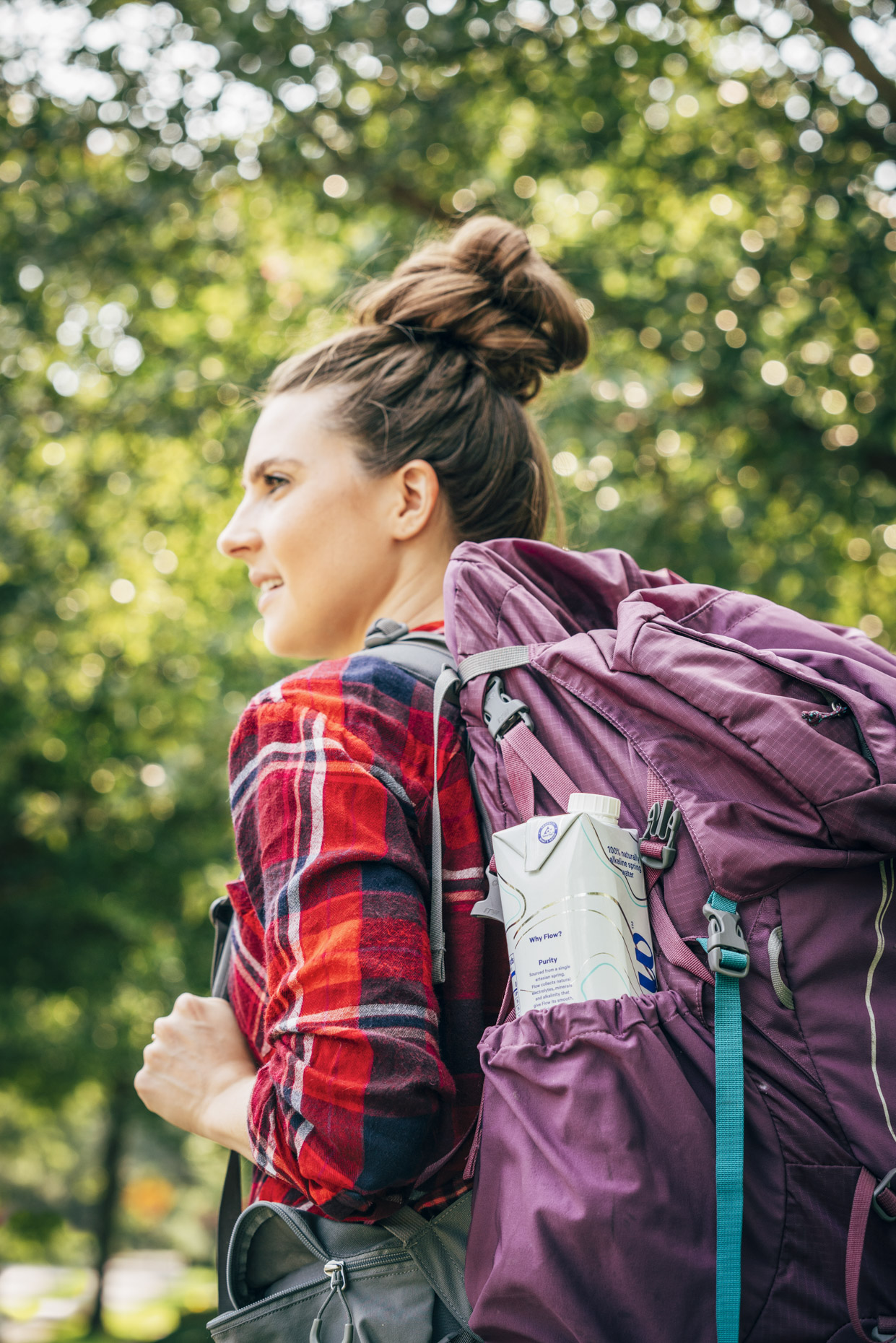 Woman hiking with box of water in backpack