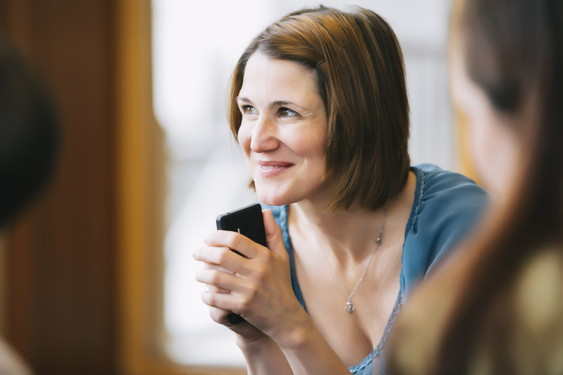 Inti St Clair photo of smiling woman in business meeting holding smartphone