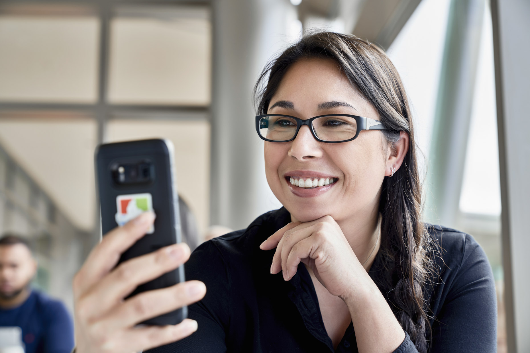 Woman in glasses smiling at cell phone