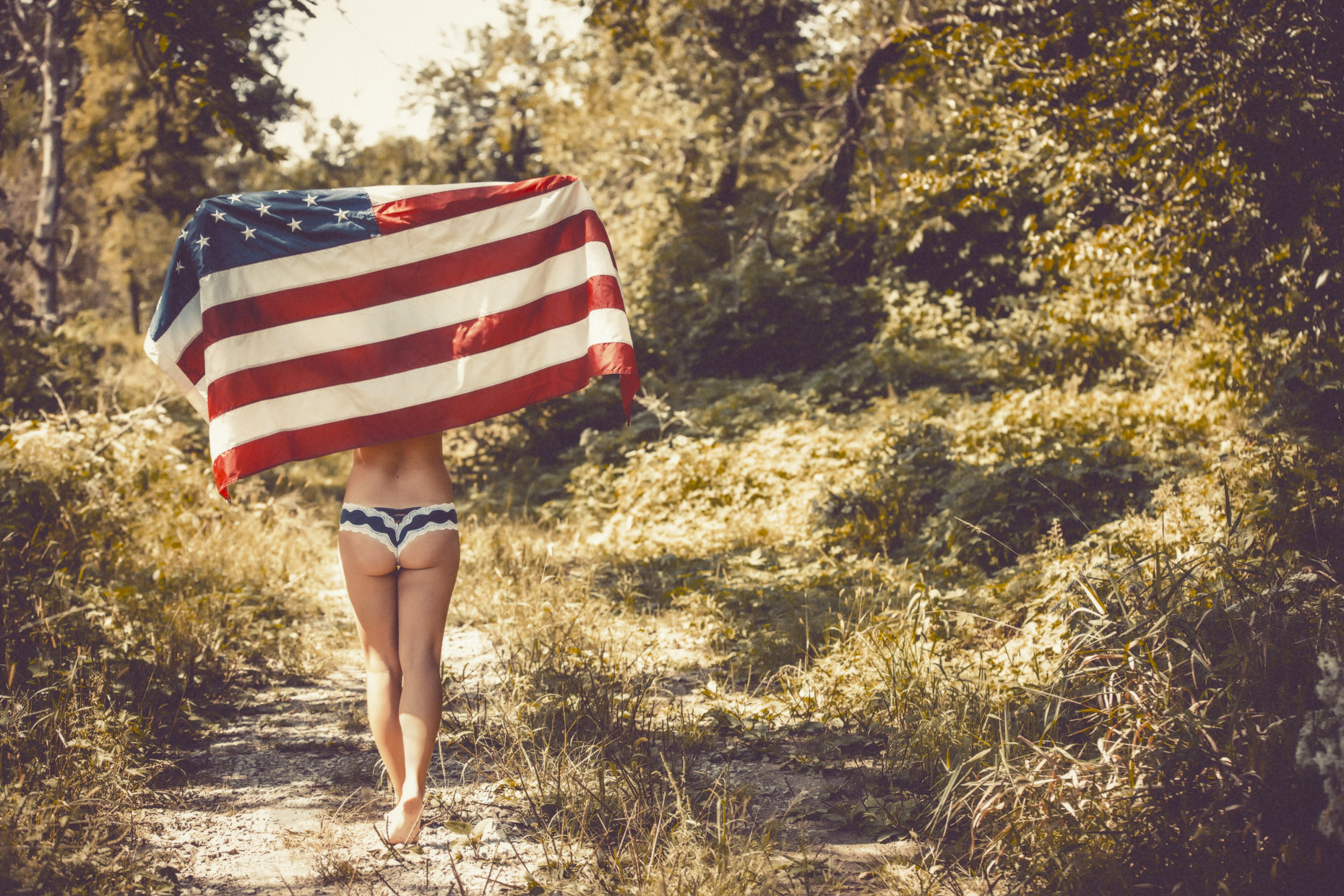 Woman in lacy underwear walking in forest holding up american flag