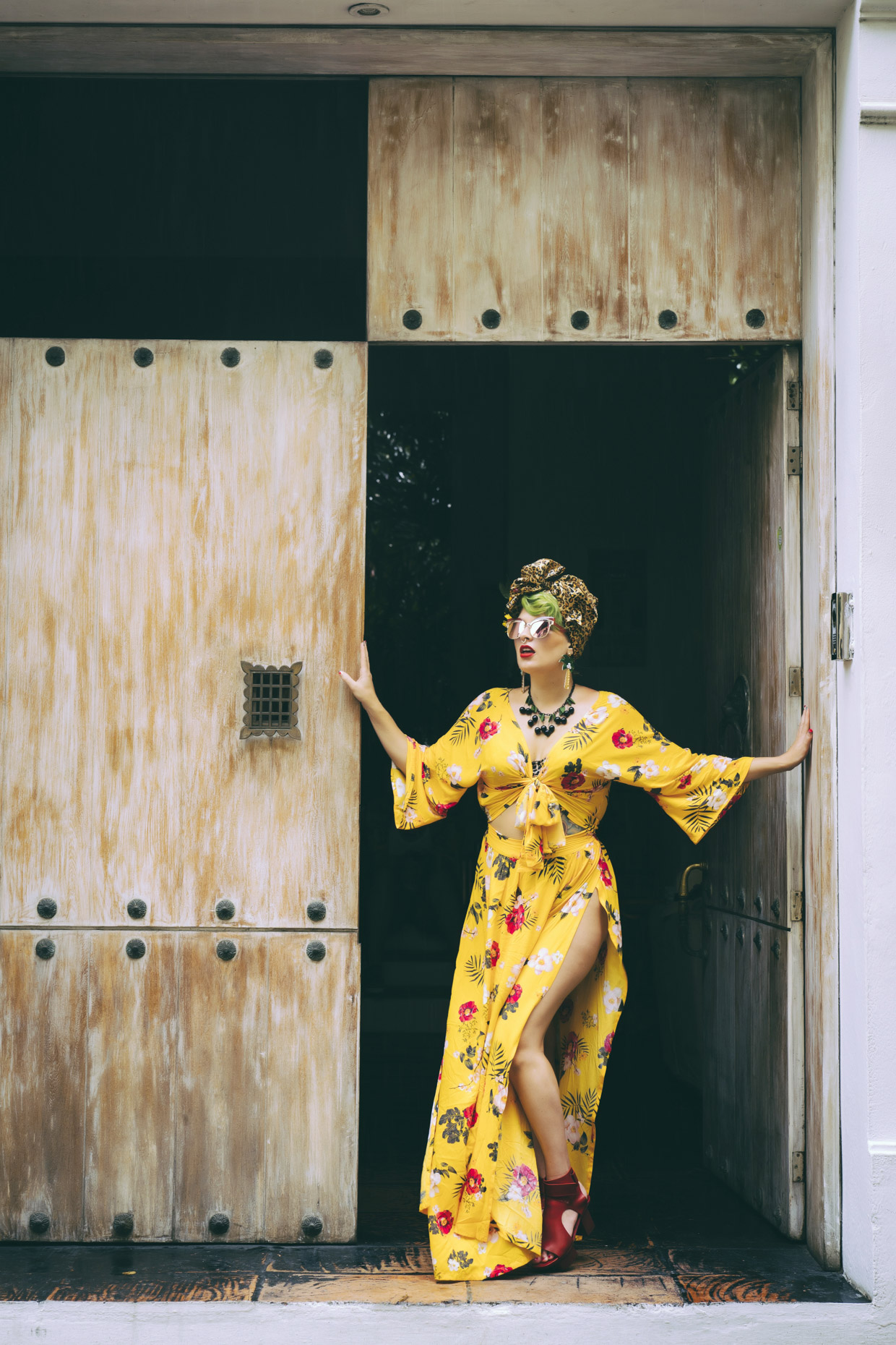 Woman in long floral dress and leopard print headwrap standing in doorway