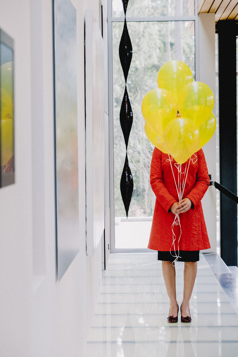 Woman in red coat standing in hallway holding yellow ballons in front of her face