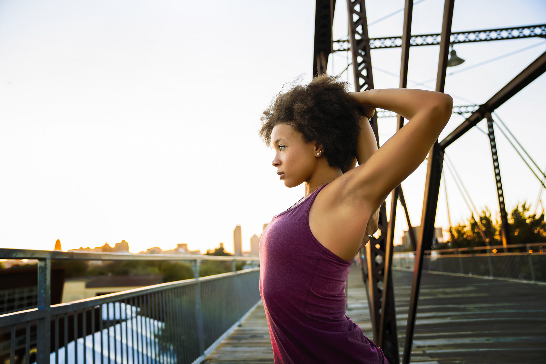 Woman in tank top stretching arms on bridge overlooking city