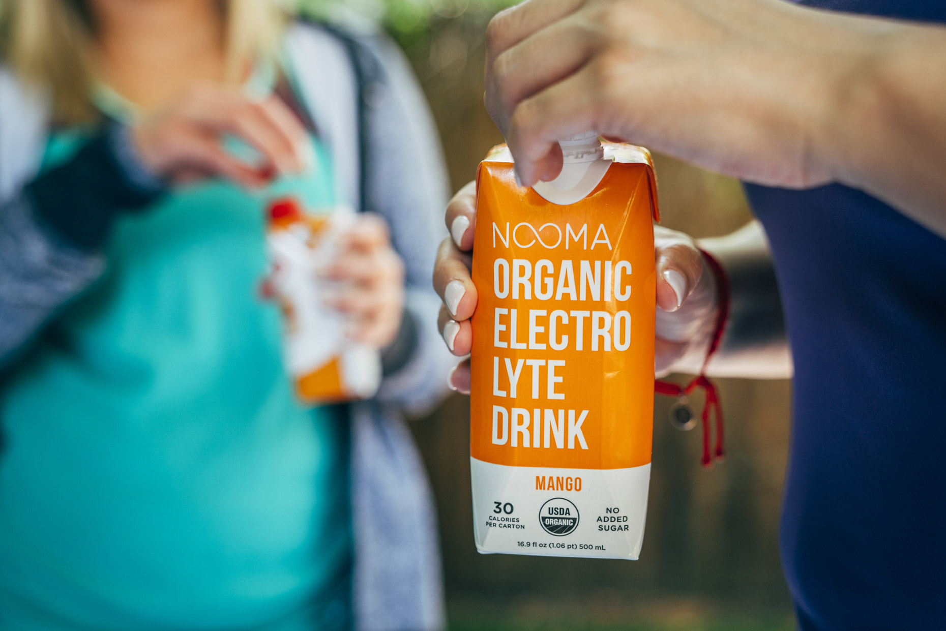 Woman in workout clothes holding Nooma mango electrolyte drink