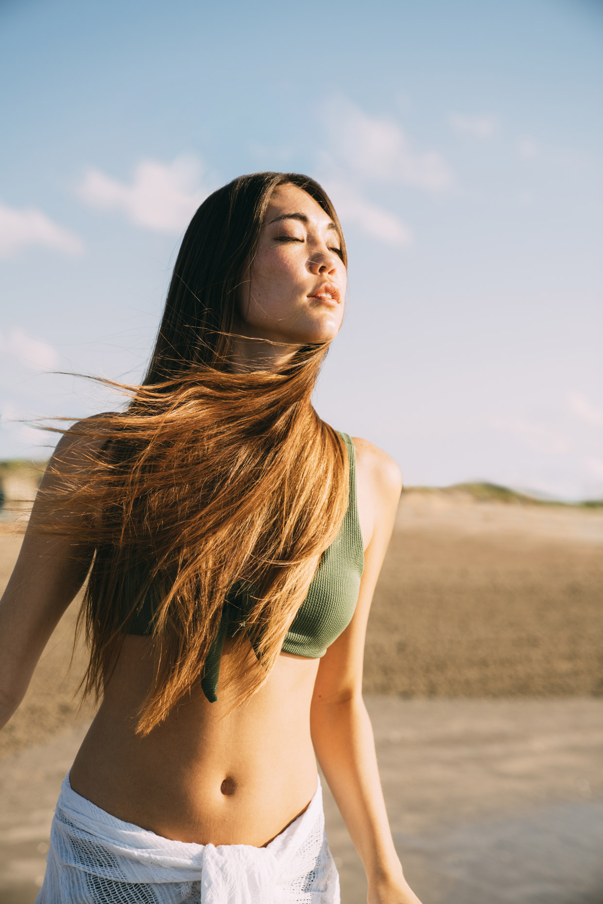Woman on beach with eyes closed and hair blowing in the wind