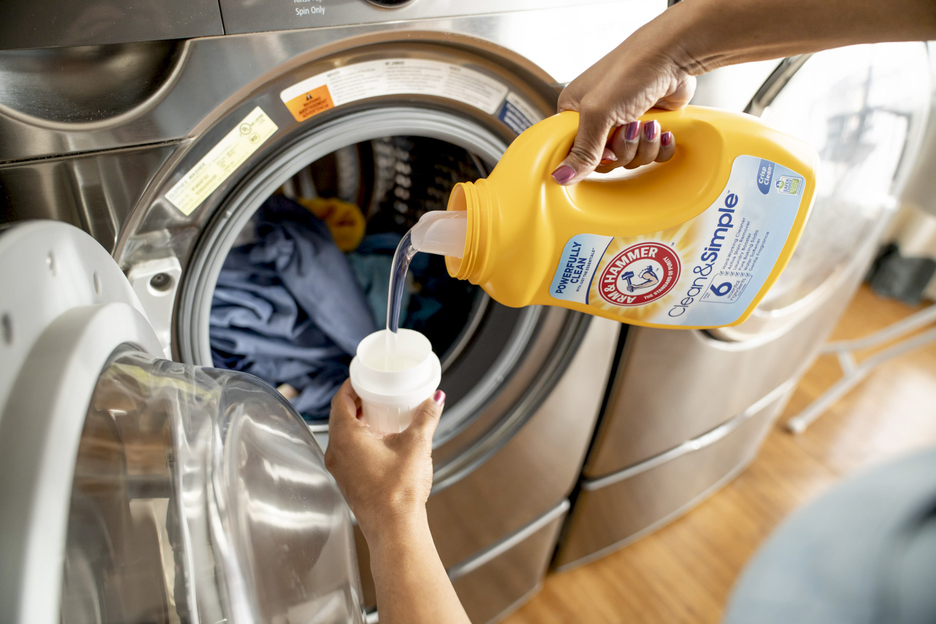 Woman pouring Arm and Hammer laundry detergent by washer
