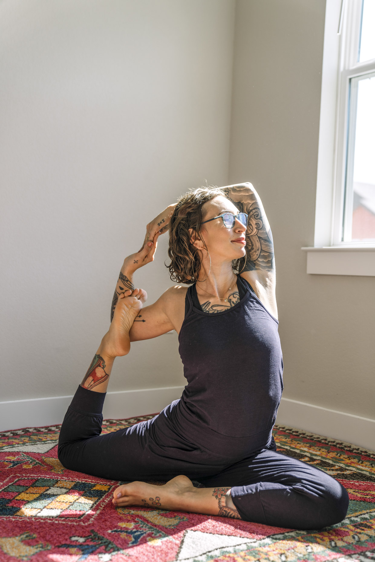 Woman practicing yoga at home in sunlight