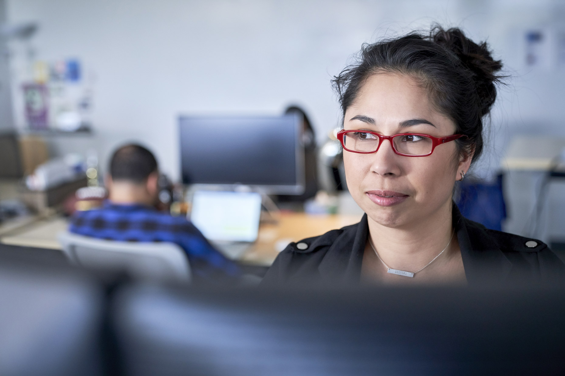Woman in red glasses in busy office looking off to side