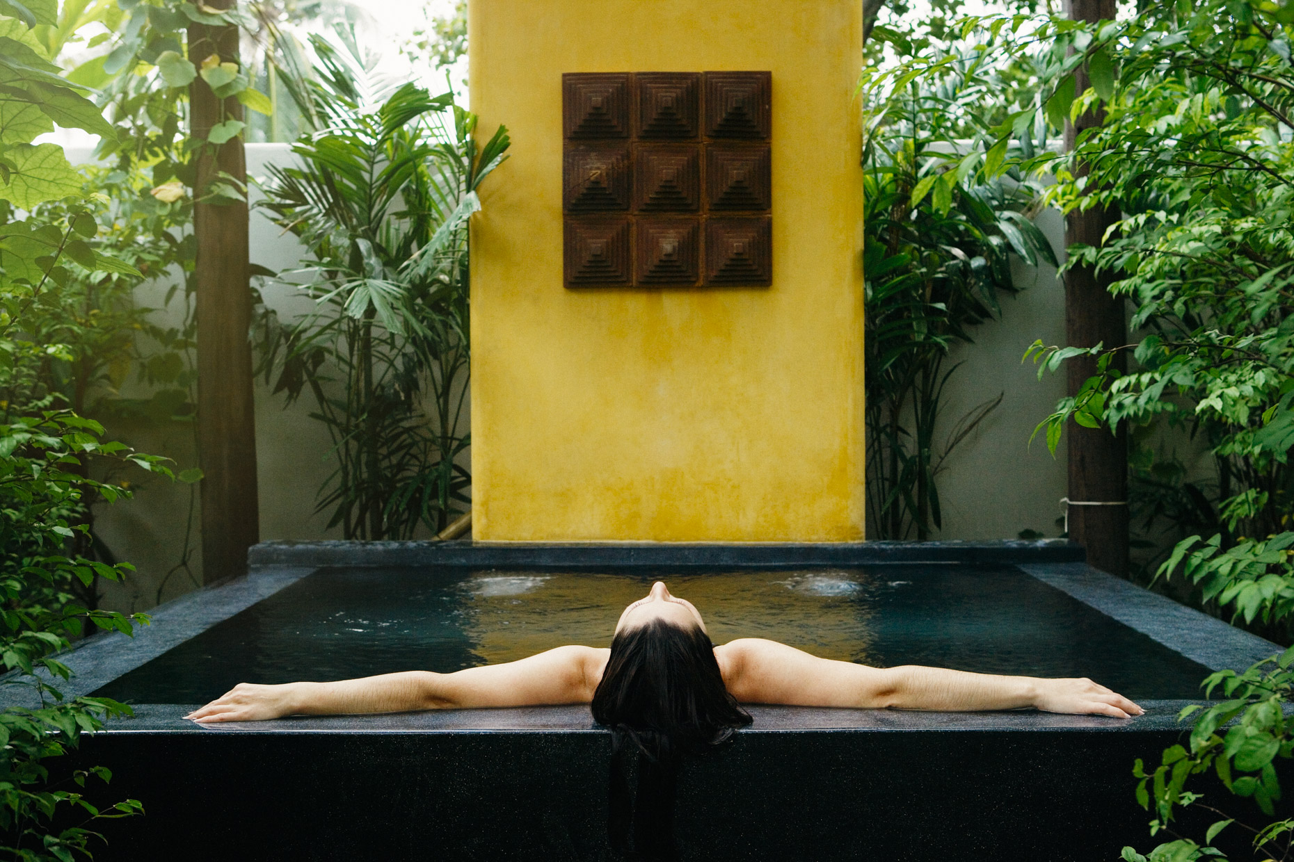 Woman relaxing in tub with arms outstretched in tropical garden