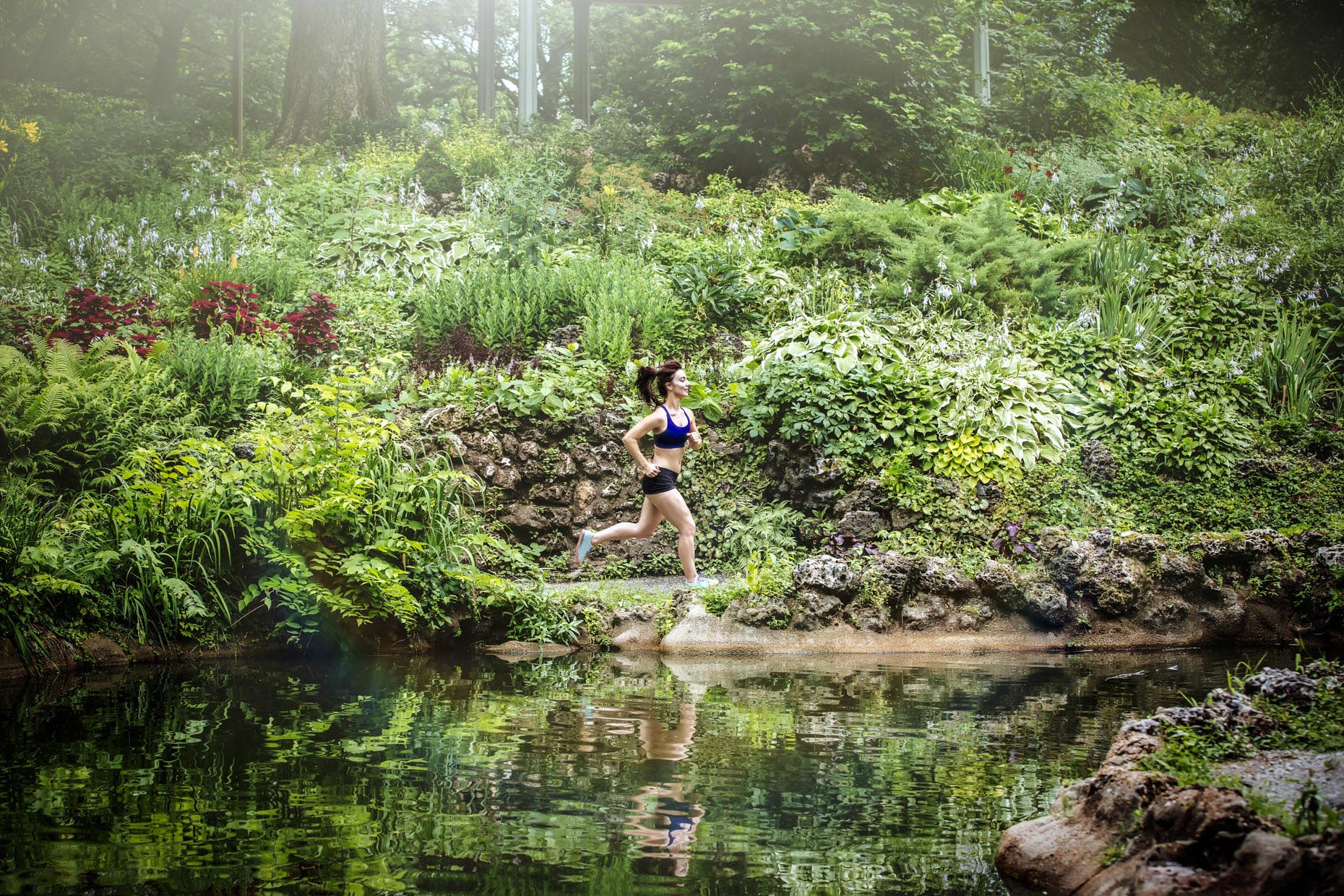 Woman running through lush park in sprintime