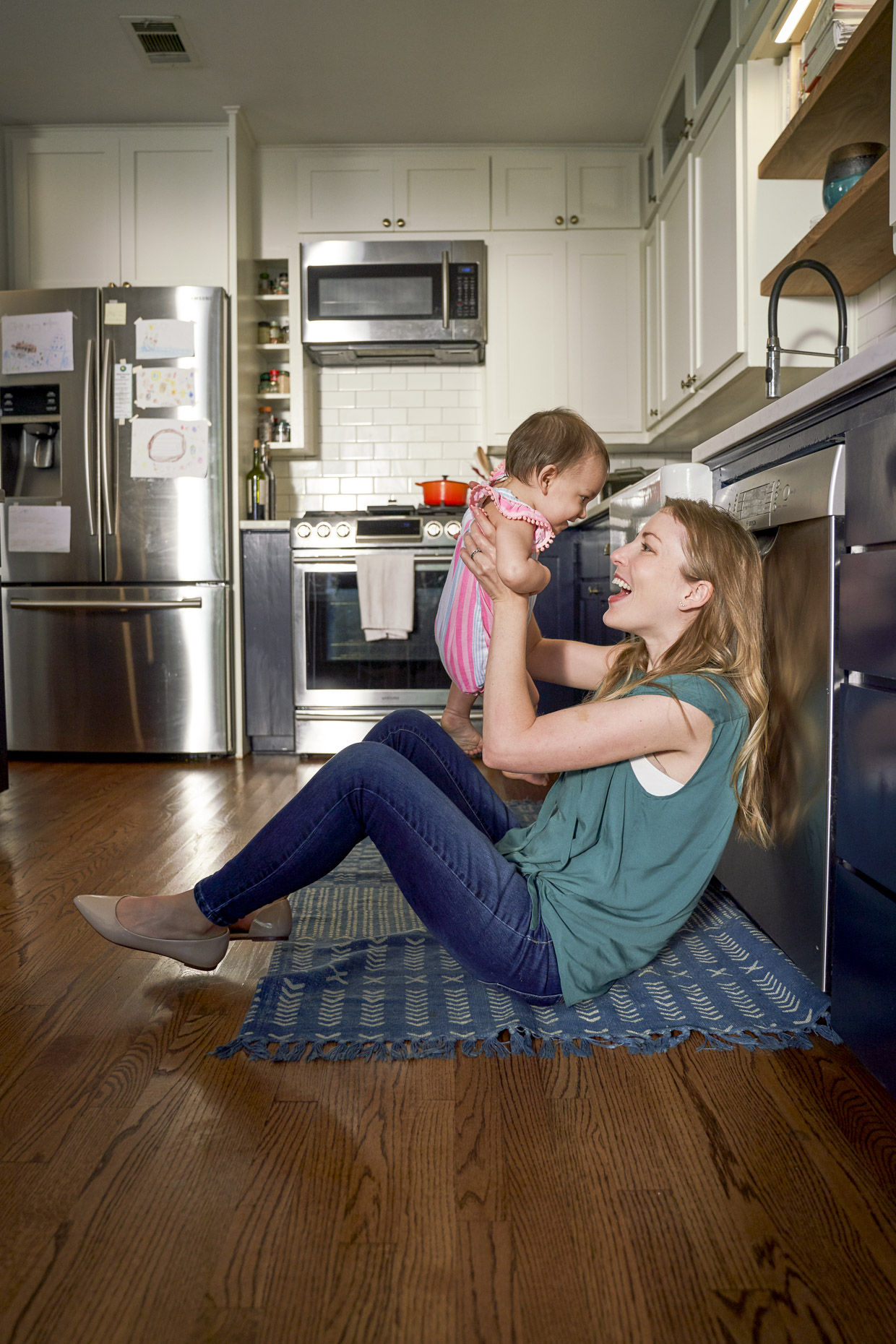 Woman sitting on floor in kitchen playing with baby