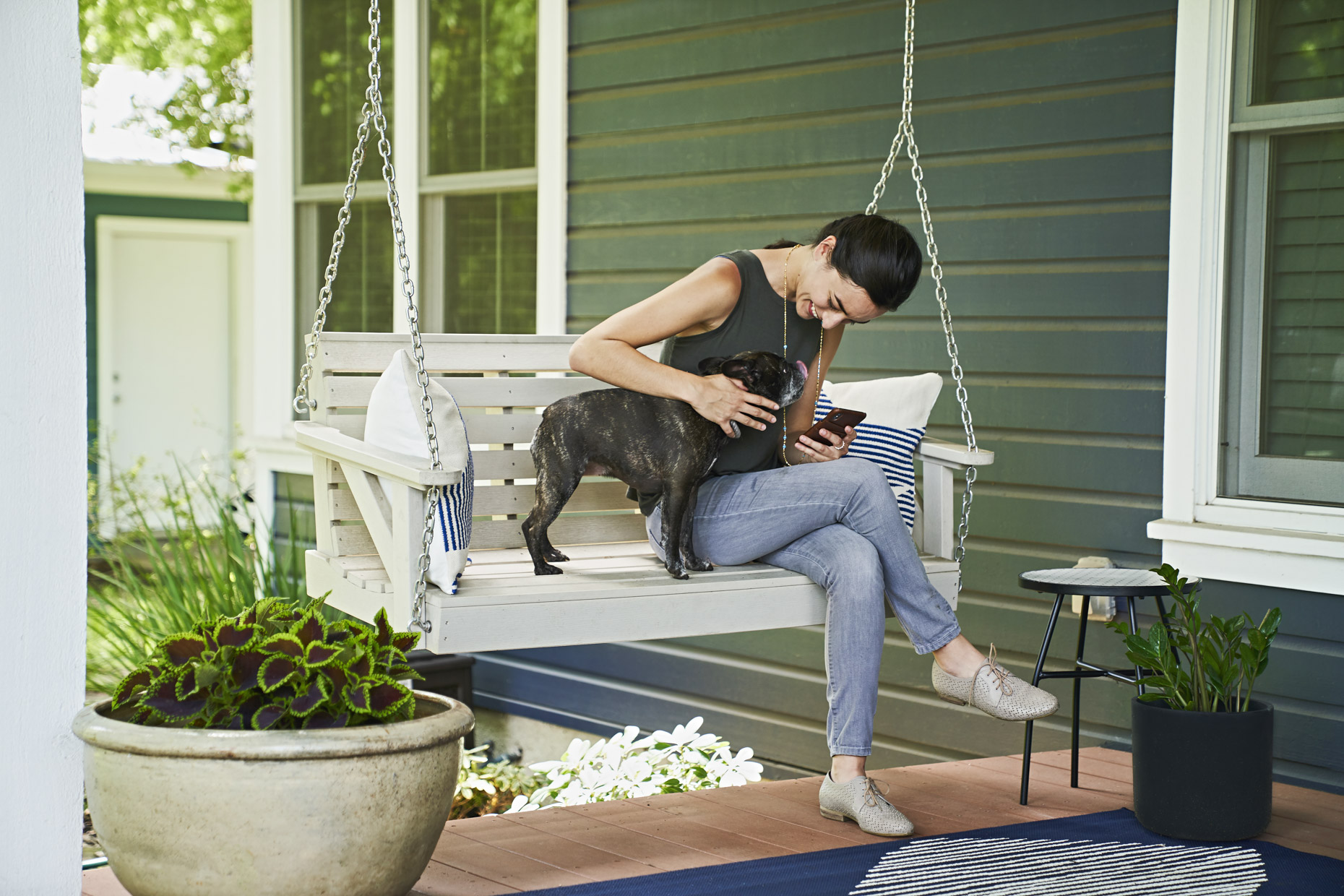 Woman sitting on porch swing petting her french bulldog