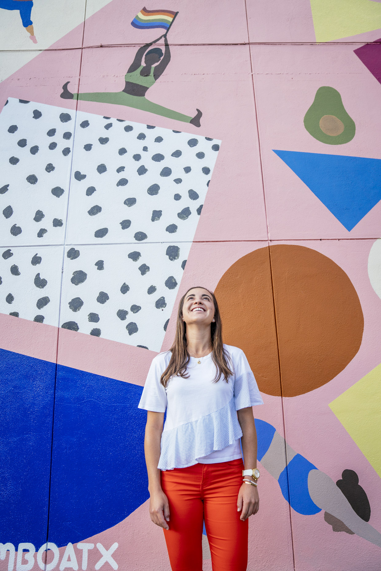 Woman standing in front of colorful wall mural looking up