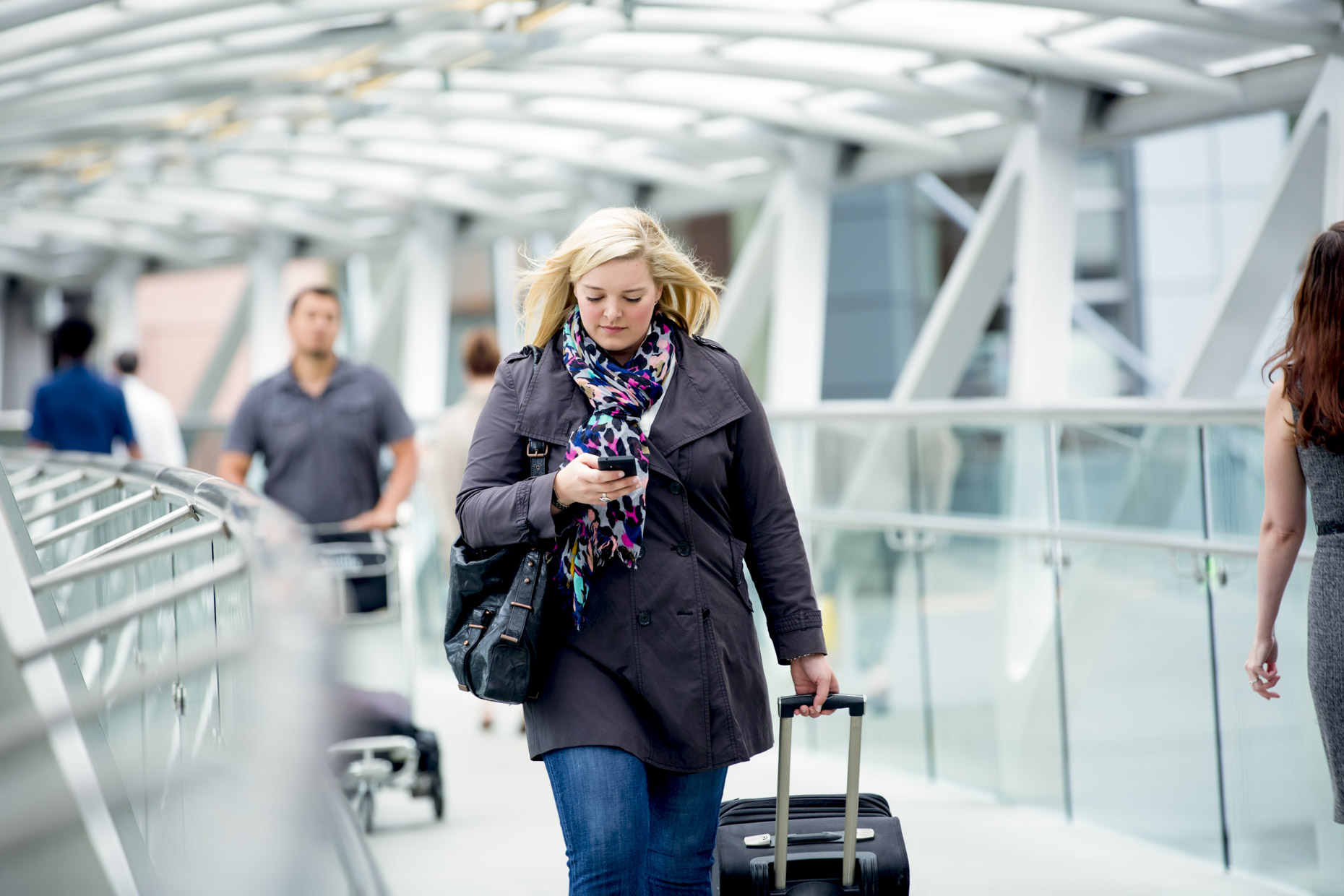 Woman walking through airport terminal looking at cell phone
